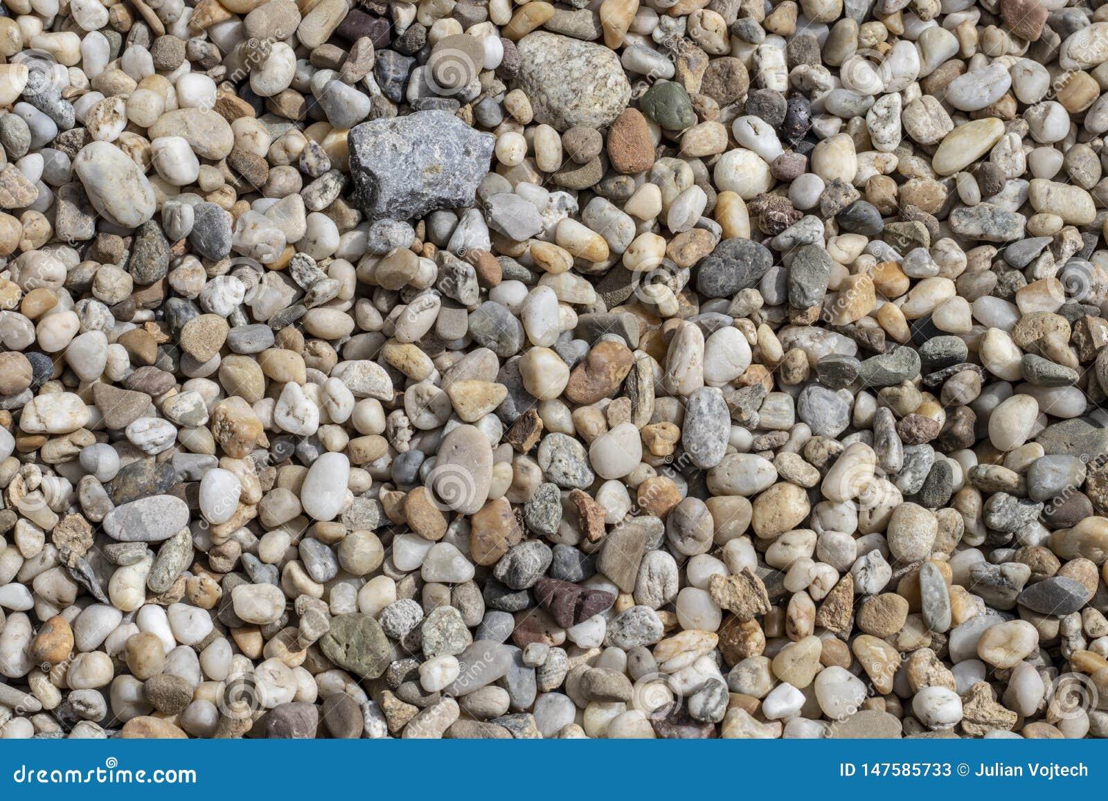Grinttextuur Kleine stenen, kleine rotsen, kiezelstenen in vele schaduwen van grijs, wit, bruin, groen en blauw