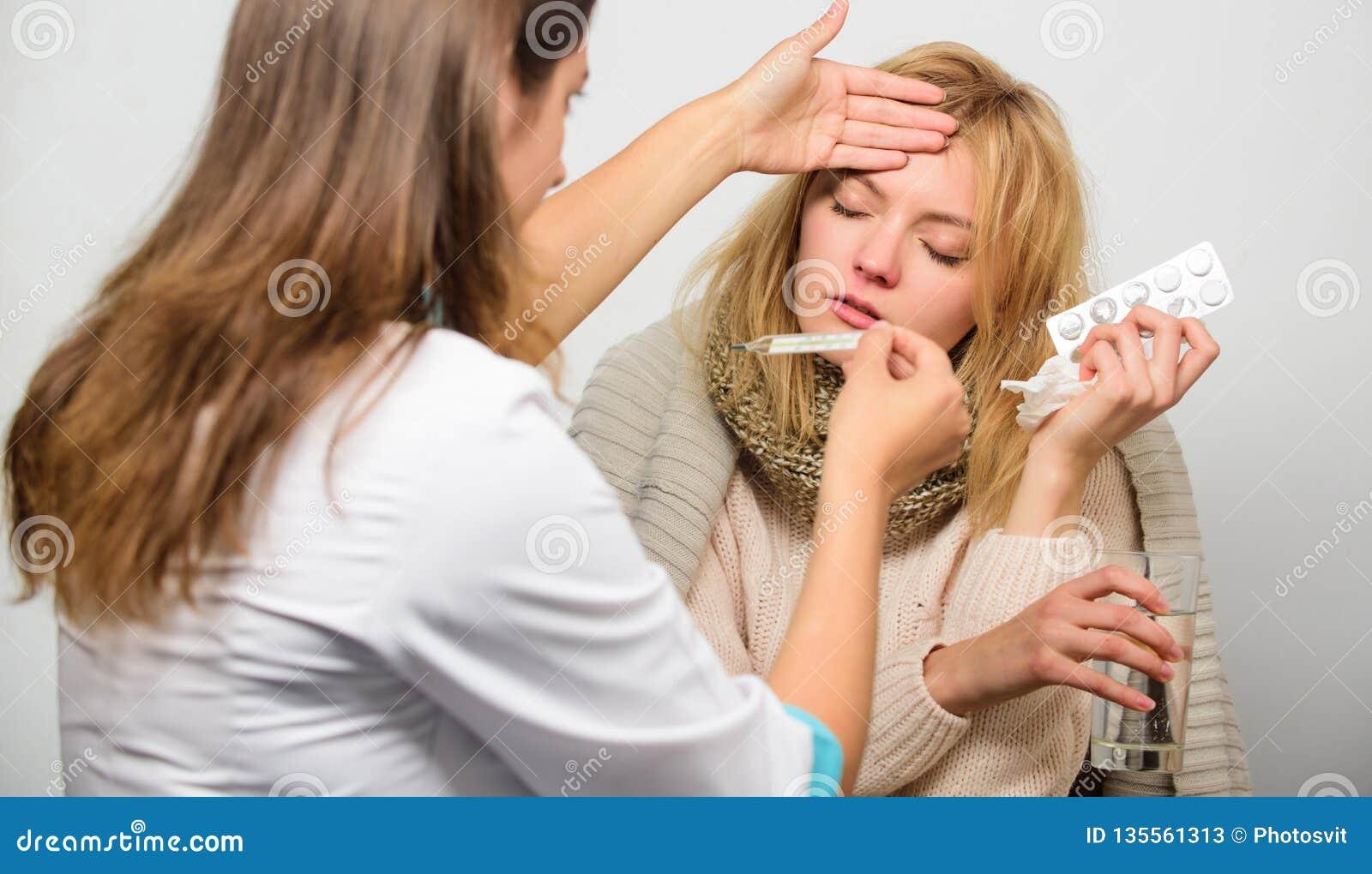 Grippe und Tiefkühlen Frau mit Doktor sich beraten Mädchen im Schal überprüft von Doktor Kälte- und Grippehilfsmittel doktor