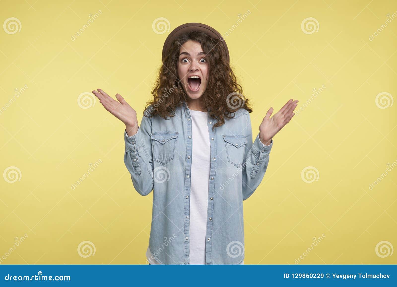 Gritar novo e mulher moreno surpreendida com cabelo encaracolado e chapéu, felizes sobre o presente novo, isolado sobre o amarelo