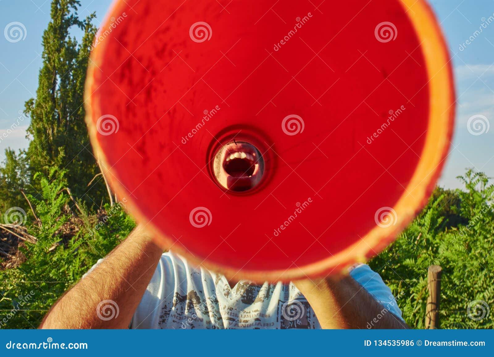 Gritaria do homem através de um tubo alaranjado