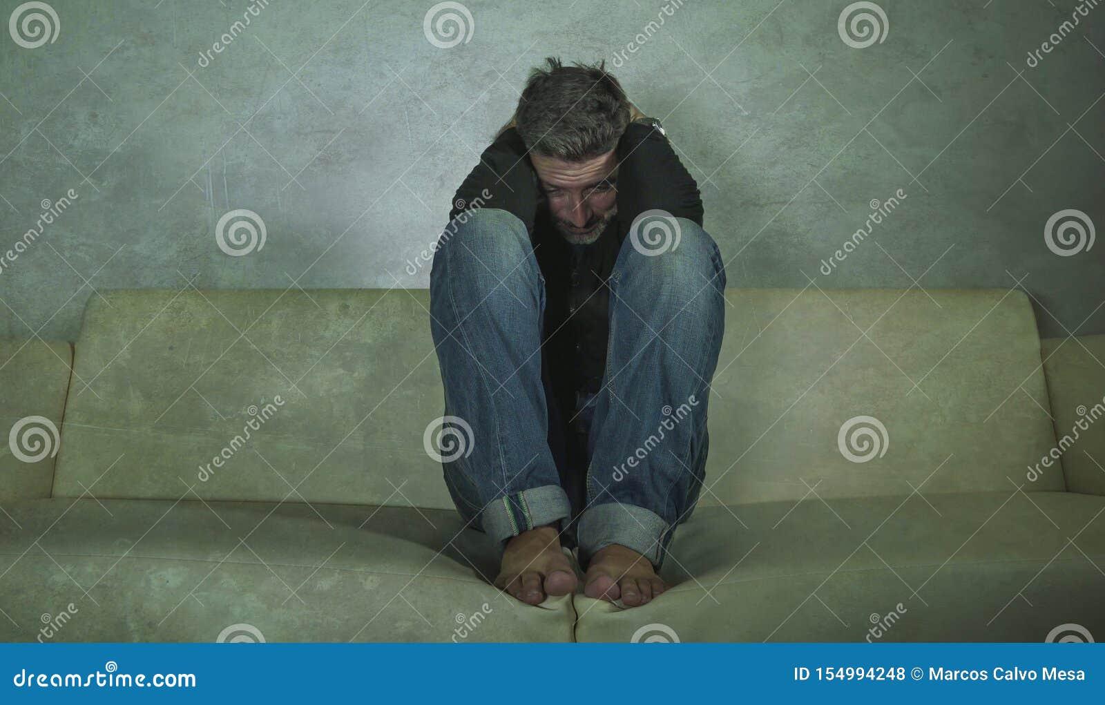 Griterío sombrío deprimido y triste atractivo joven del sofá del hombre en casa perdido en crisis y la depresión de la ansiedad d