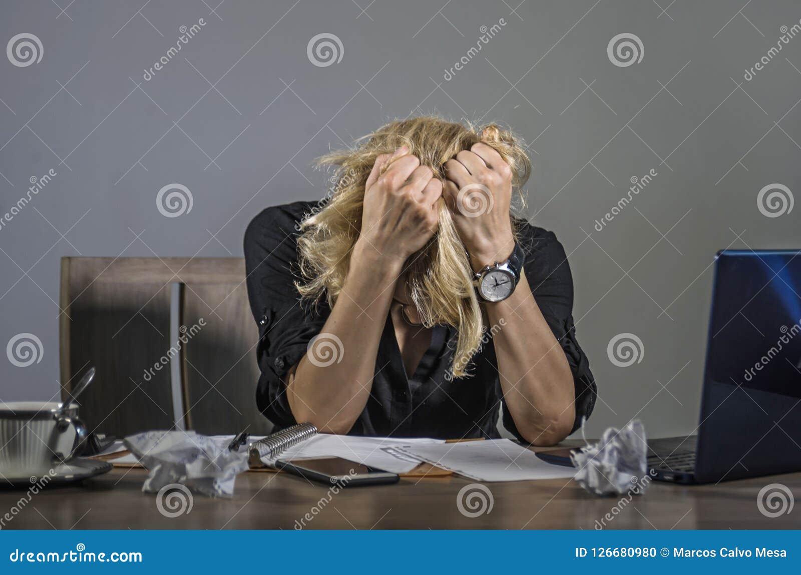 Grito frustrante e forçado novo da mulher de negócio triste na mesa de escritório que trabalha com o laptop oprimido pelo workl d