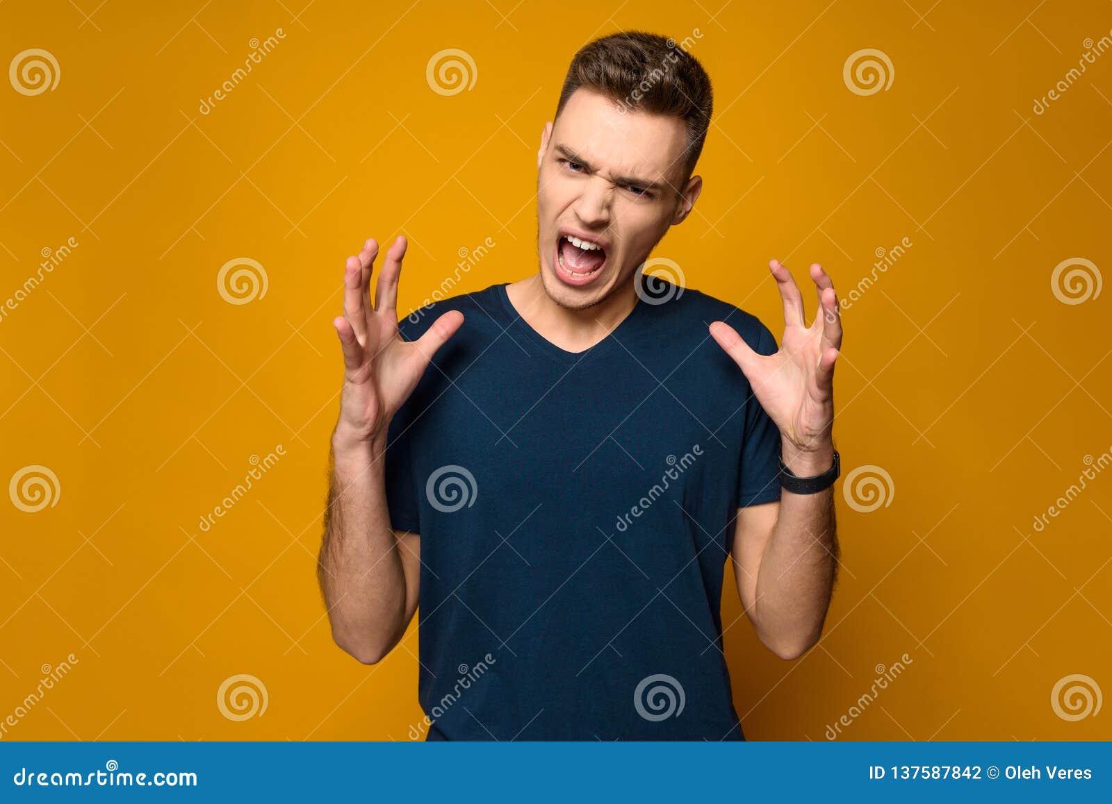 Gritos consideráveis novos do indivíduo que gesticulam com mãos
