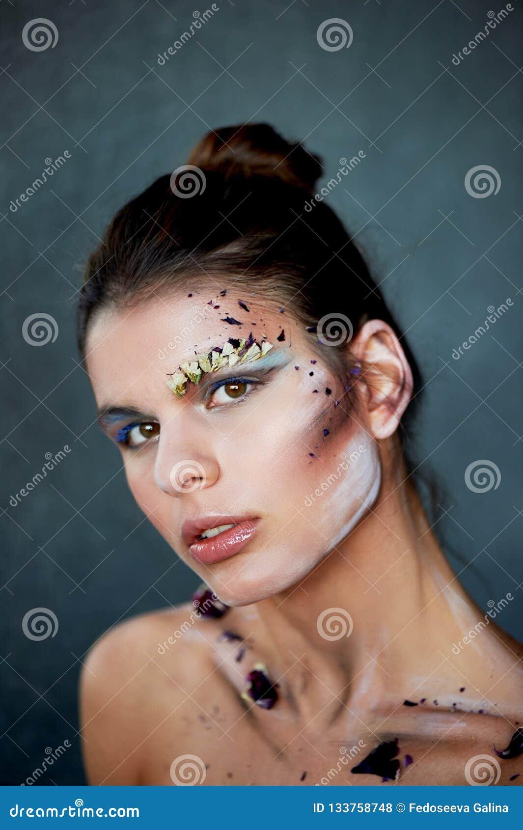 Groß-Gesichtsporträt Abstriche auf ihrem Gesicht Das Make-up unter Verwendung der trockenen Farben Kreative Persönlichkeit, Model