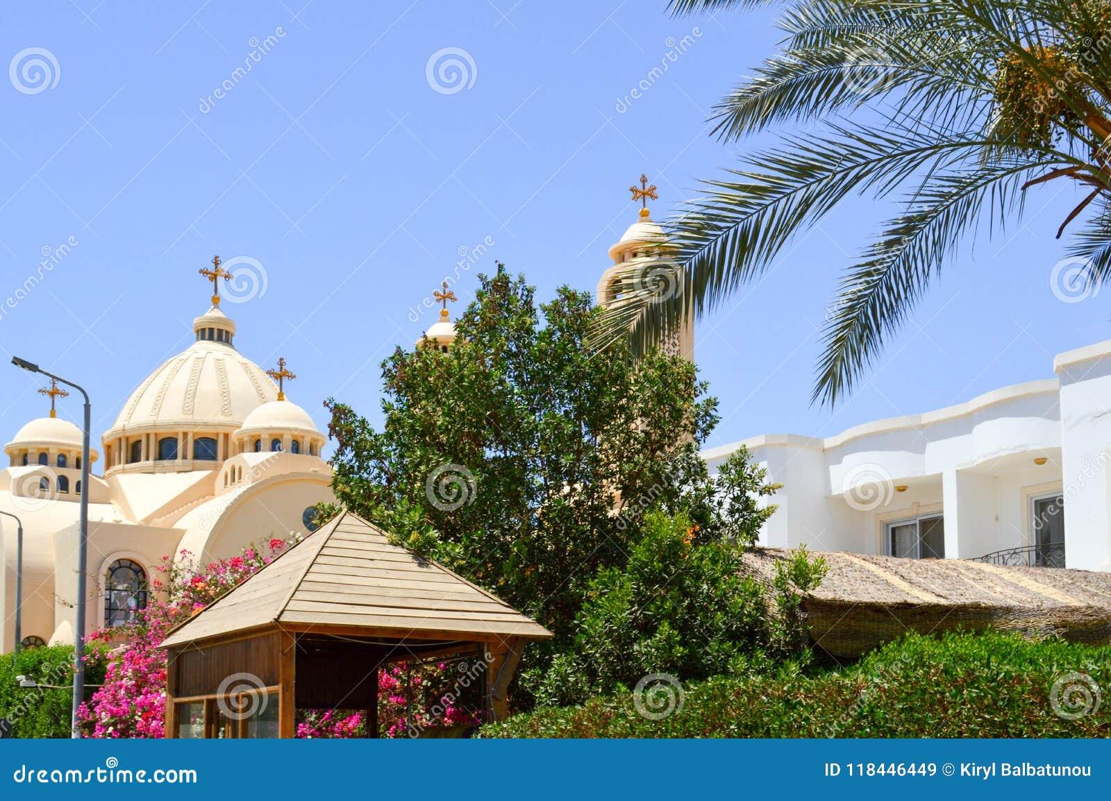 Große ägyptische orthodoxe weiße Kirche mit Kreuzen, Bögen, Hauben und Gebetsfenstern gegen den Hintergrund von grünen Bäumen und