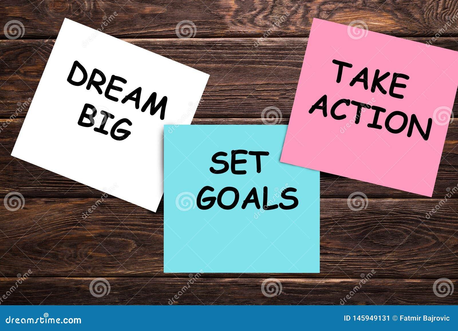 Gro?e, gesetzte Traumziele, nehmen Aktionskonzept - Motivrat oder Anzeige auf bunten klebrigen Anmerkungen ?ber Holztisch