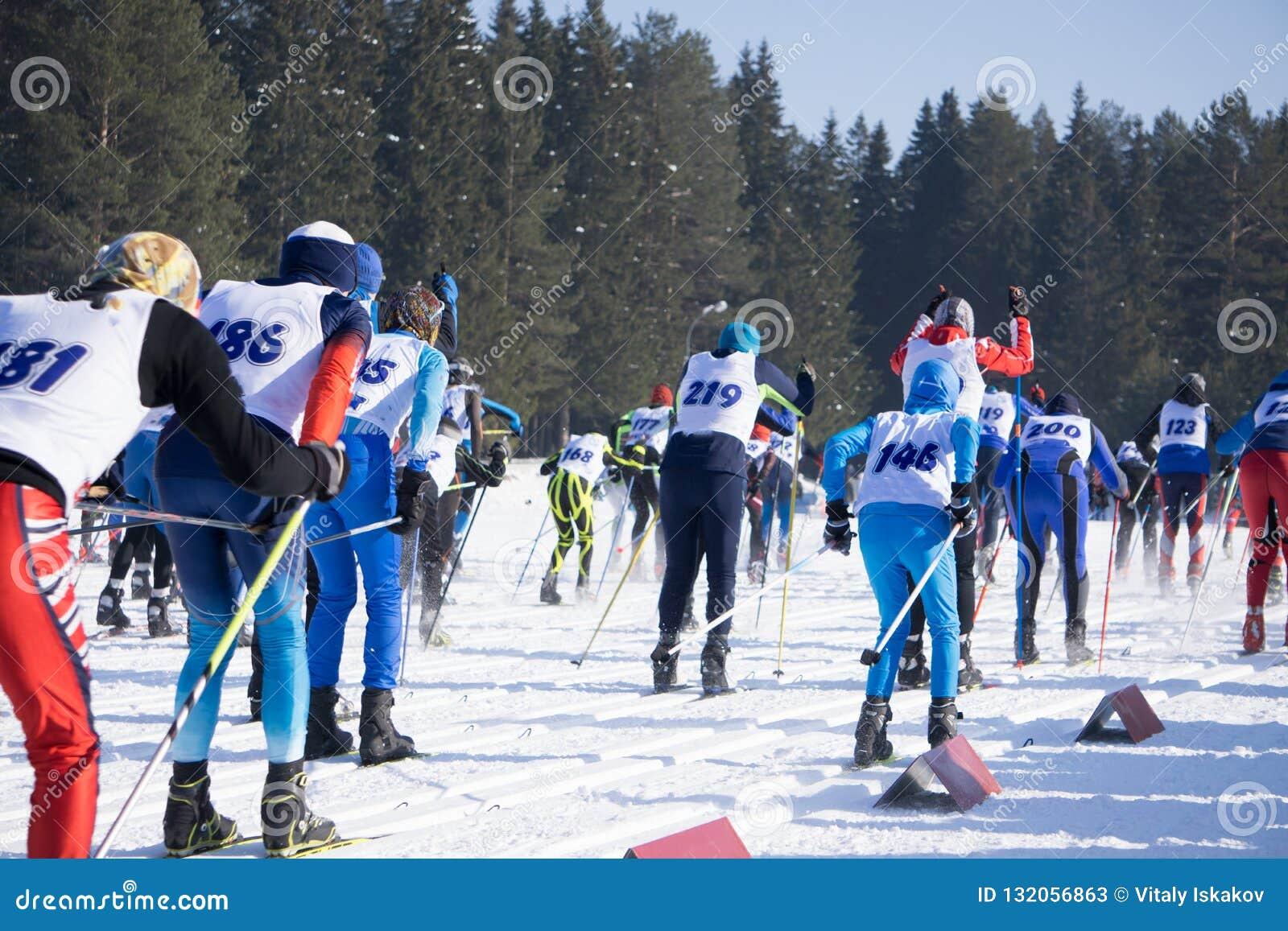 Große Gruppe Skifahrer auf Ski neigt sich in einen Höhenkurort im Winter