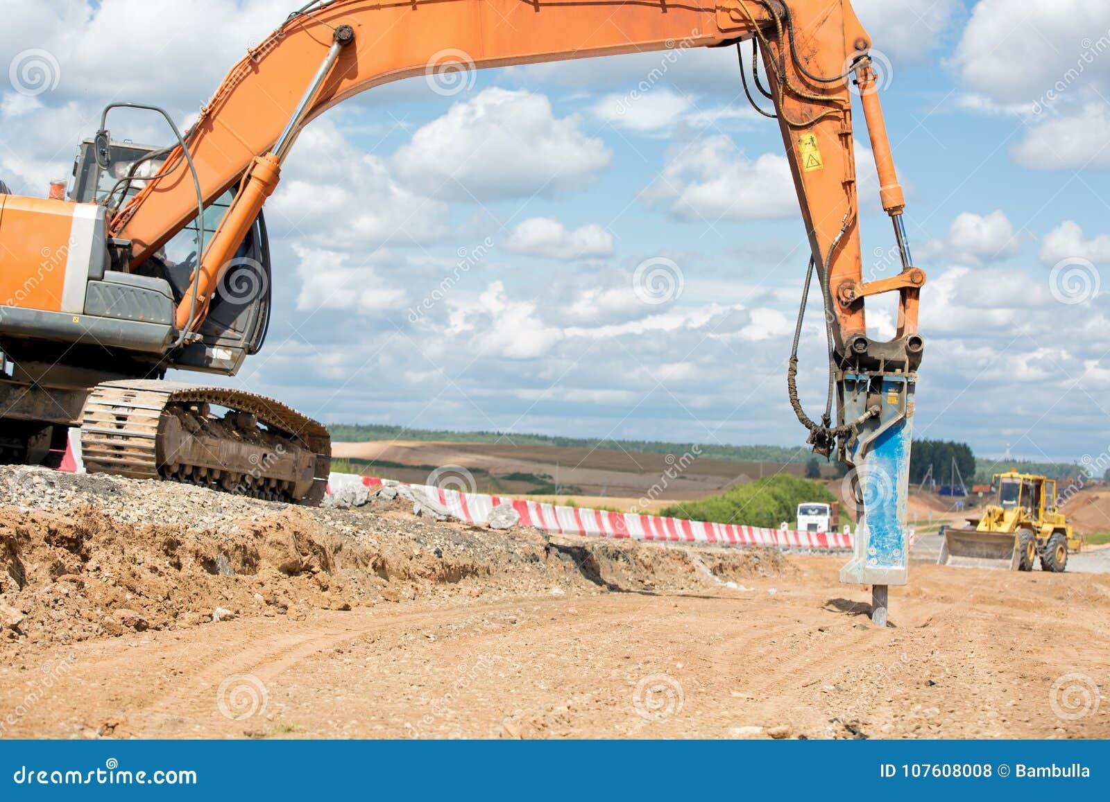 Große Jackhammermaschine, welche die Asphaltpflasterung zerquetscht