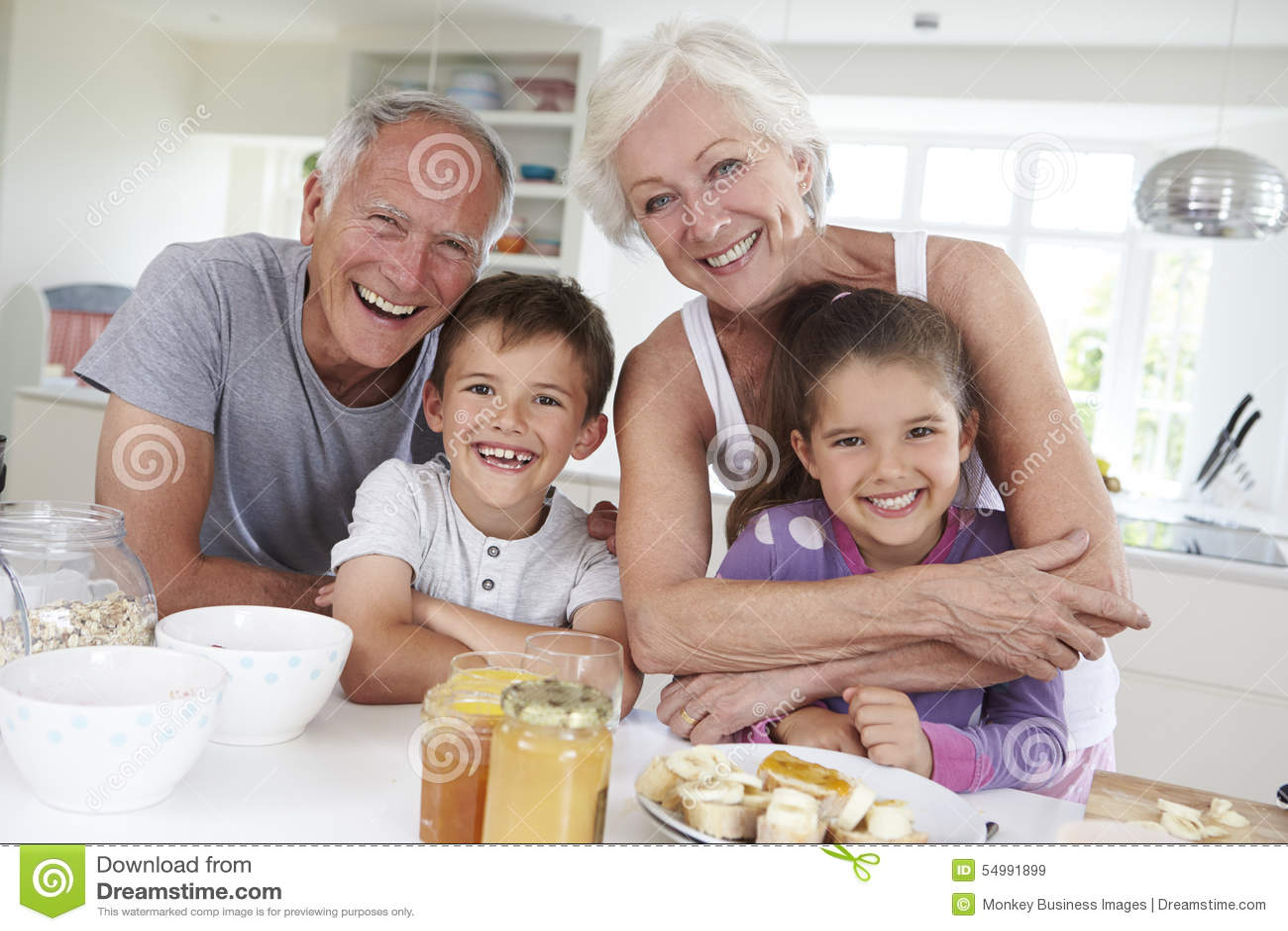 Großeltern mit den Enkelkindern, die Frühstück in der Küche essen