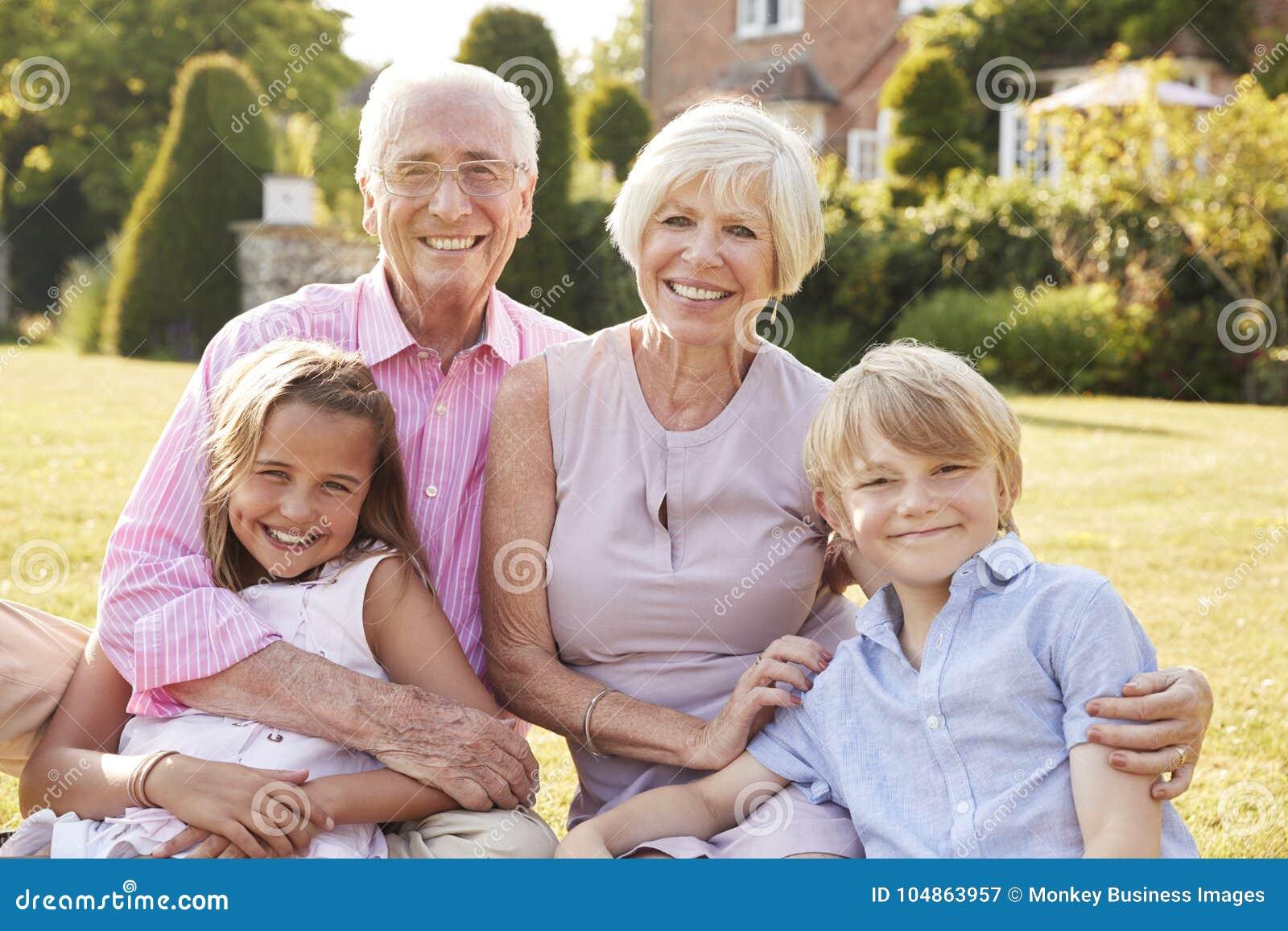 Großeltern und Enkelkinder, die auf Gras in einem Garten sitzen