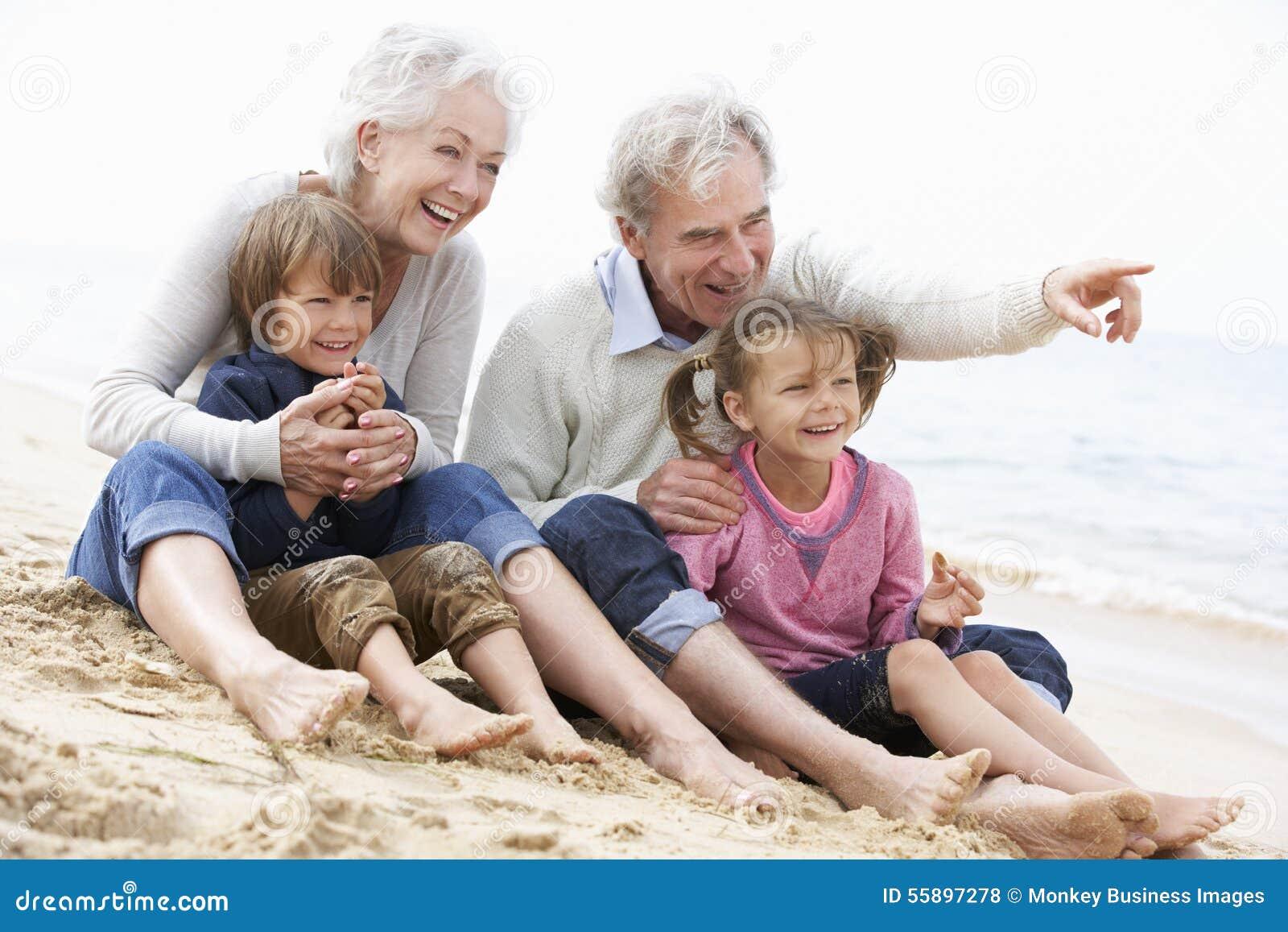 Großeltern und Enkelkinder, die zusammen auf Strand sitzen