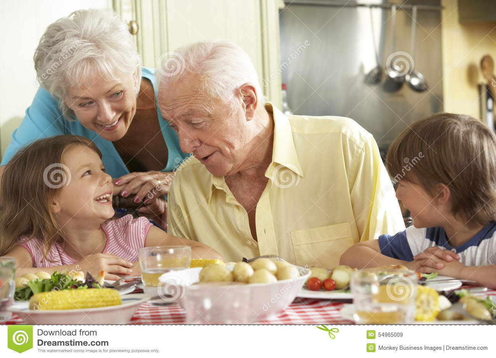 Großeltern und Enkelkinder, die zusammen Mahlzeit in der Küche essen
