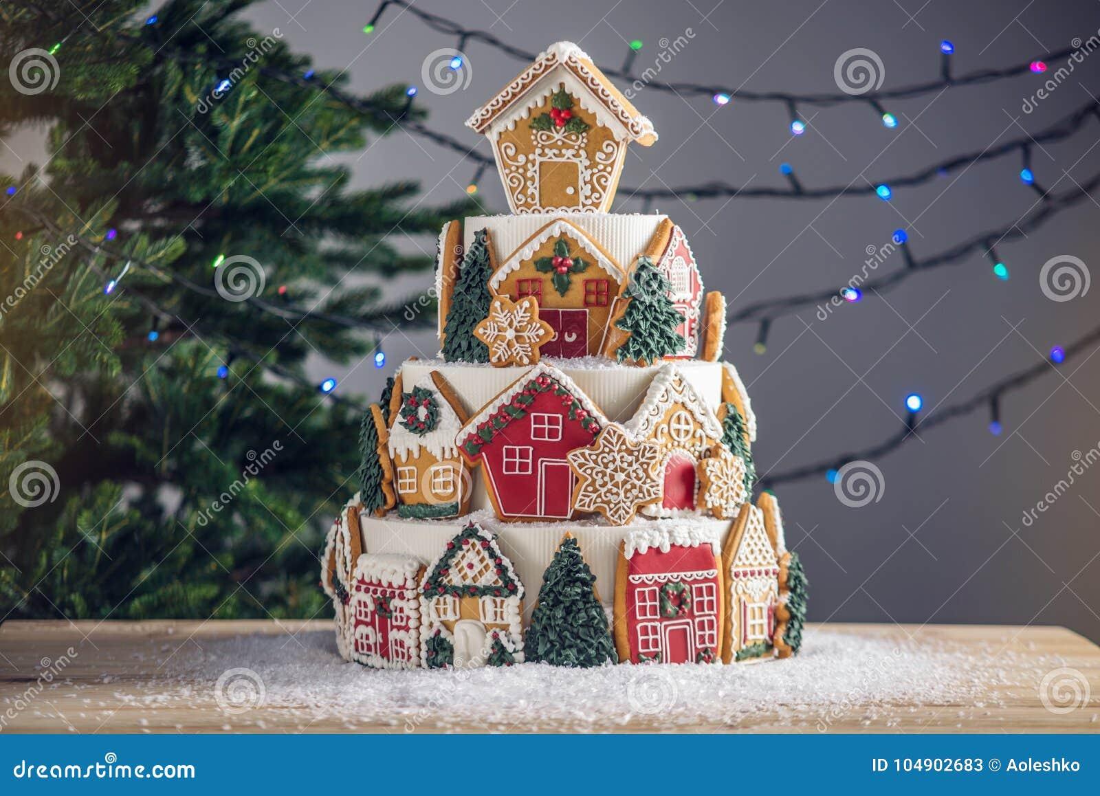 Großer abgestufter Weihnachtskuchen verziert mit Lebkuchenplätzchen und ein Haus auf die Oberseite Baum und Girlanden im Hintergr