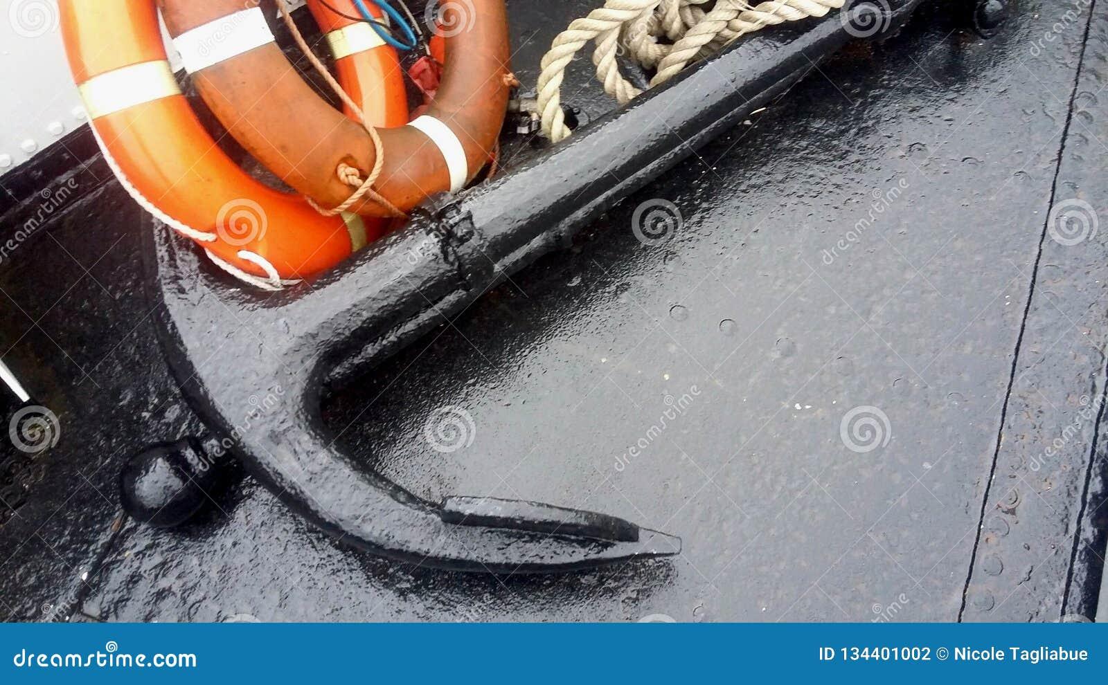 Großer Anker der Nahaufnahme O f, Rettungsgürtel und Seemannseil auf einem Boot im meeres- Nordsafe, Warnung, Rettungsboot, Notko