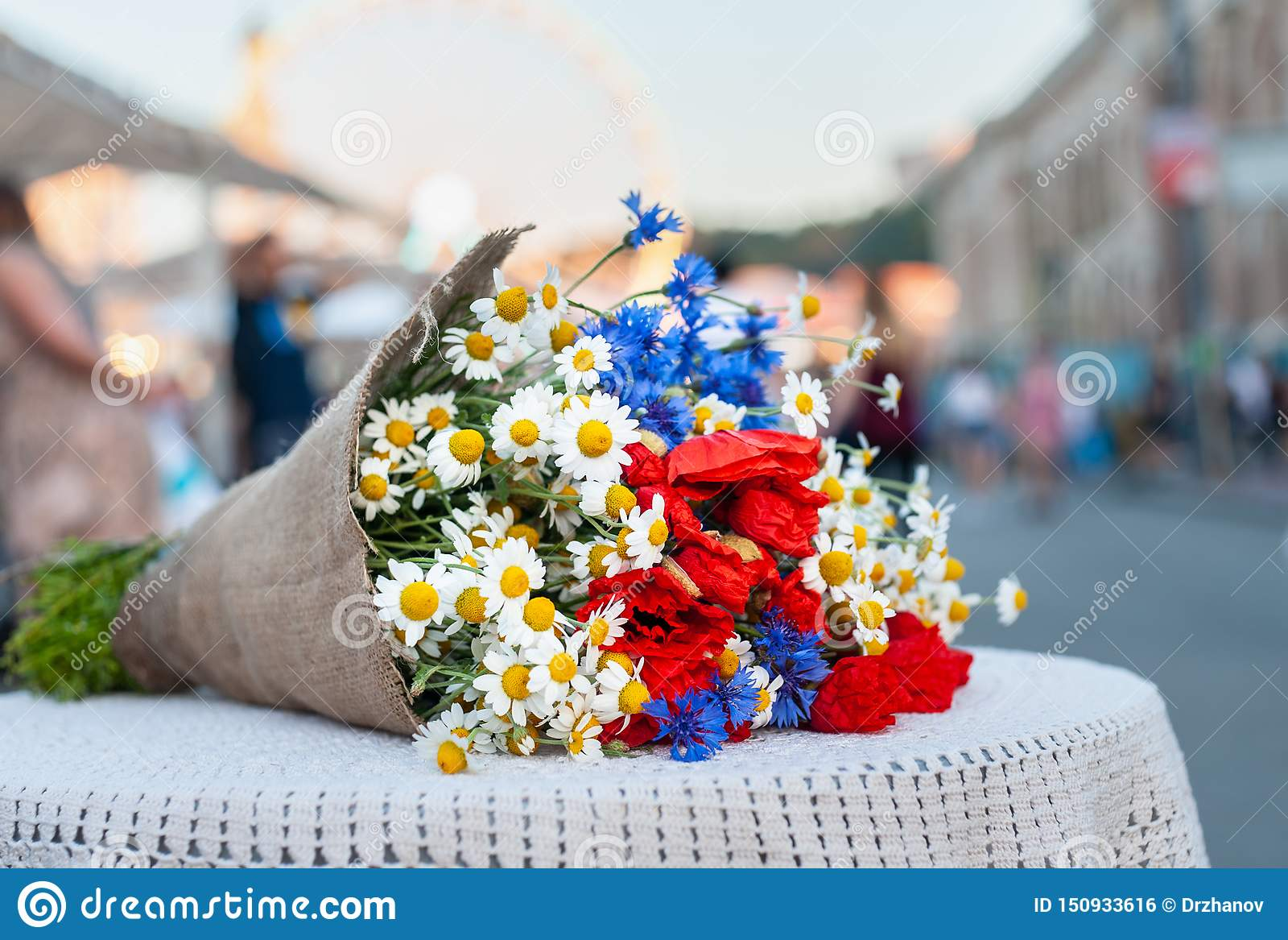 Großer Blumenstrauß von Wildflowers (Kamille, Flockenblume, Mohnblume) legt auf dem Tisch mit azurblauer weißer Tischdecke auf un