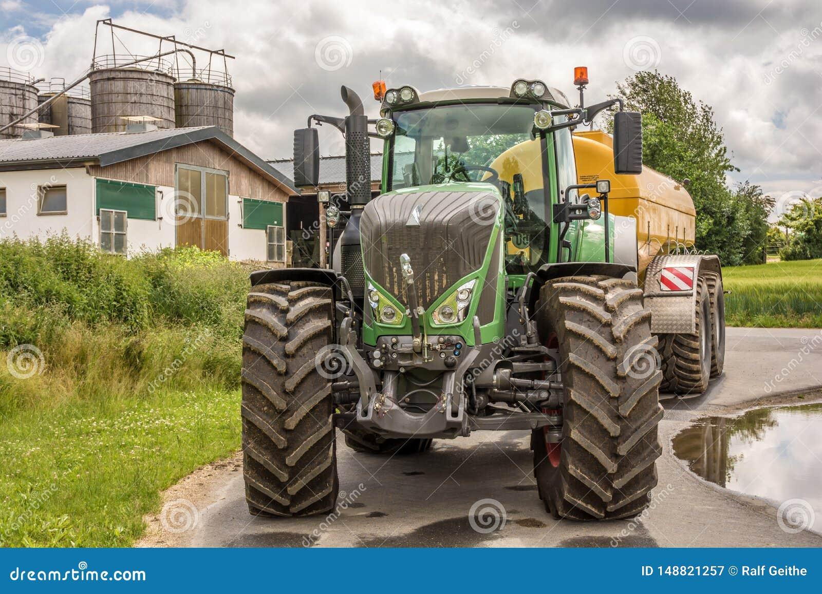 Großer kräftiger Traktor mit Bauernhof im Hintergrund