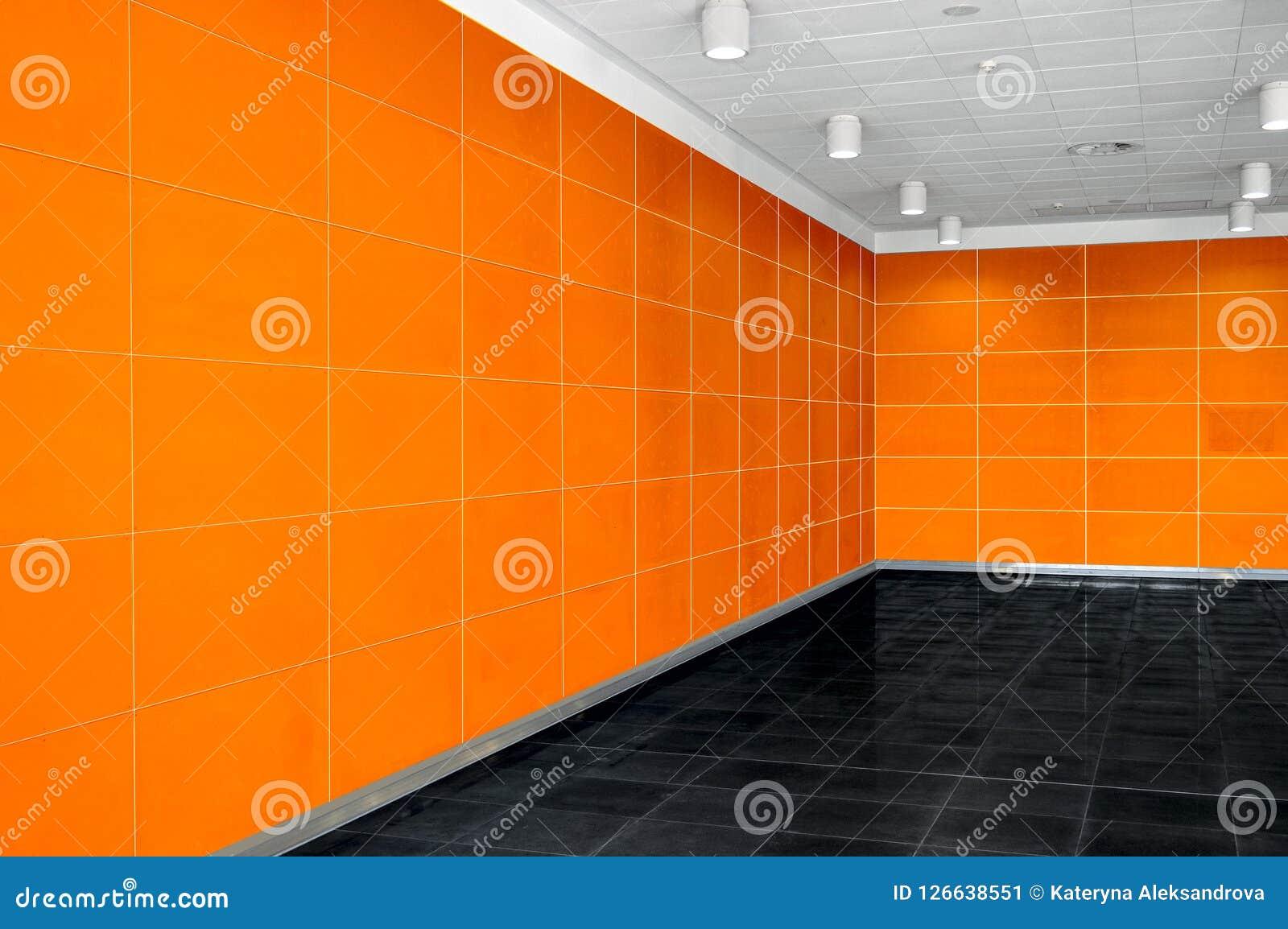 Großer leerer Rauminnenraum mit Leuchtorangewand, whire Decke a