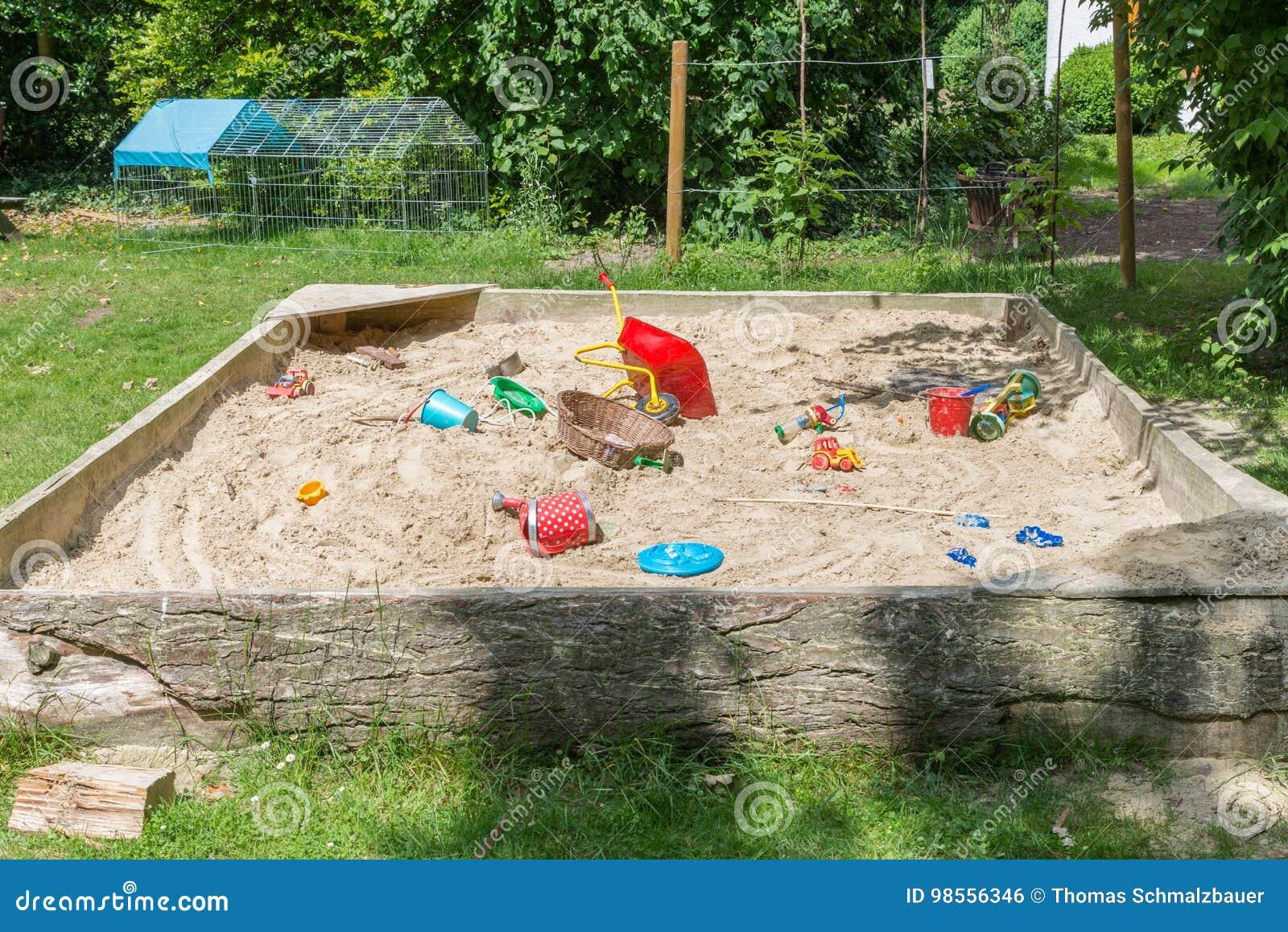 großer sandkasten mit vielen spielwaren in einem garten stockfoto