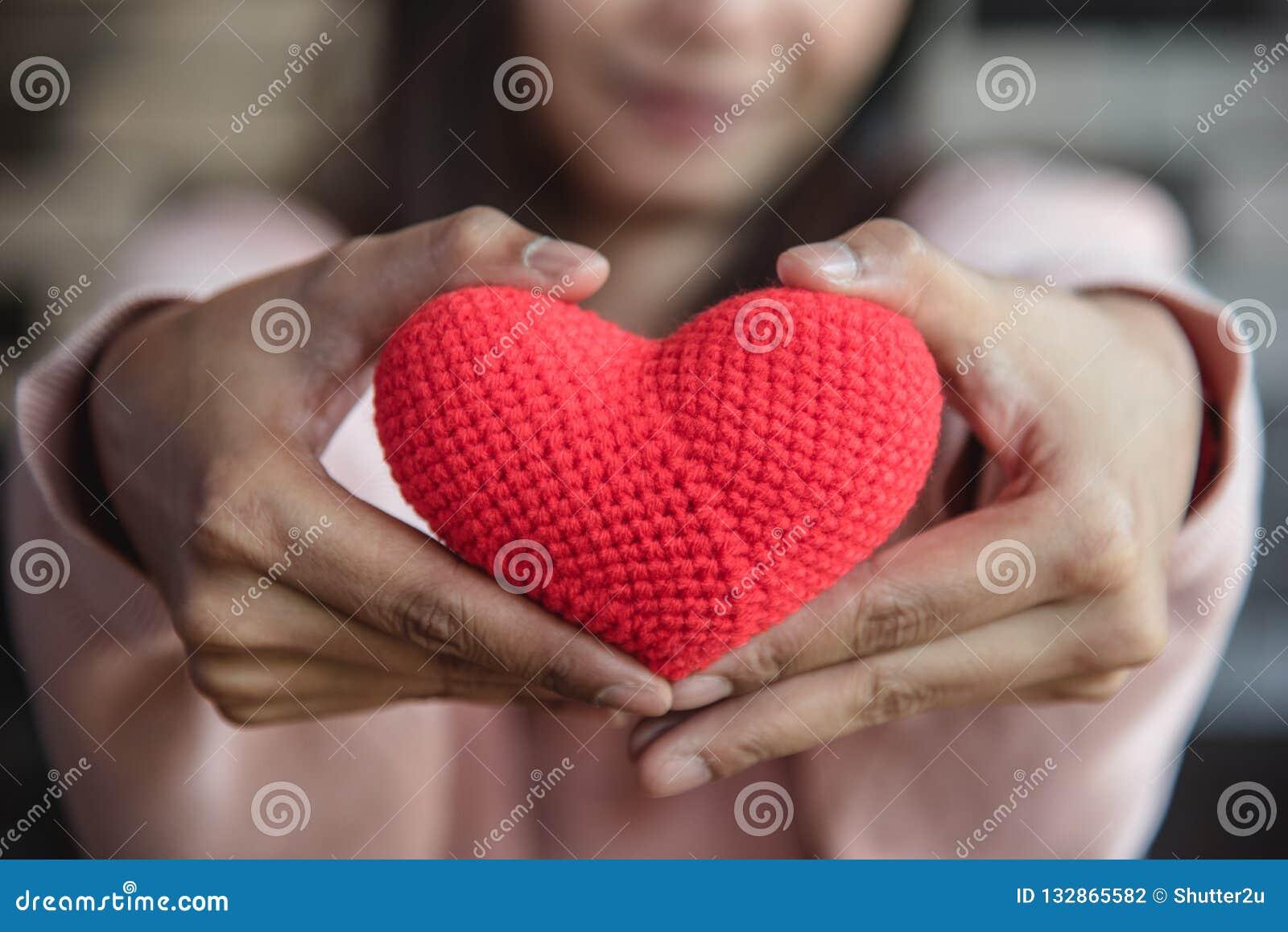 Großes rotes Garnherz, das hält und, das gibt, um durch Frauenhand zu konfrontieren Lo