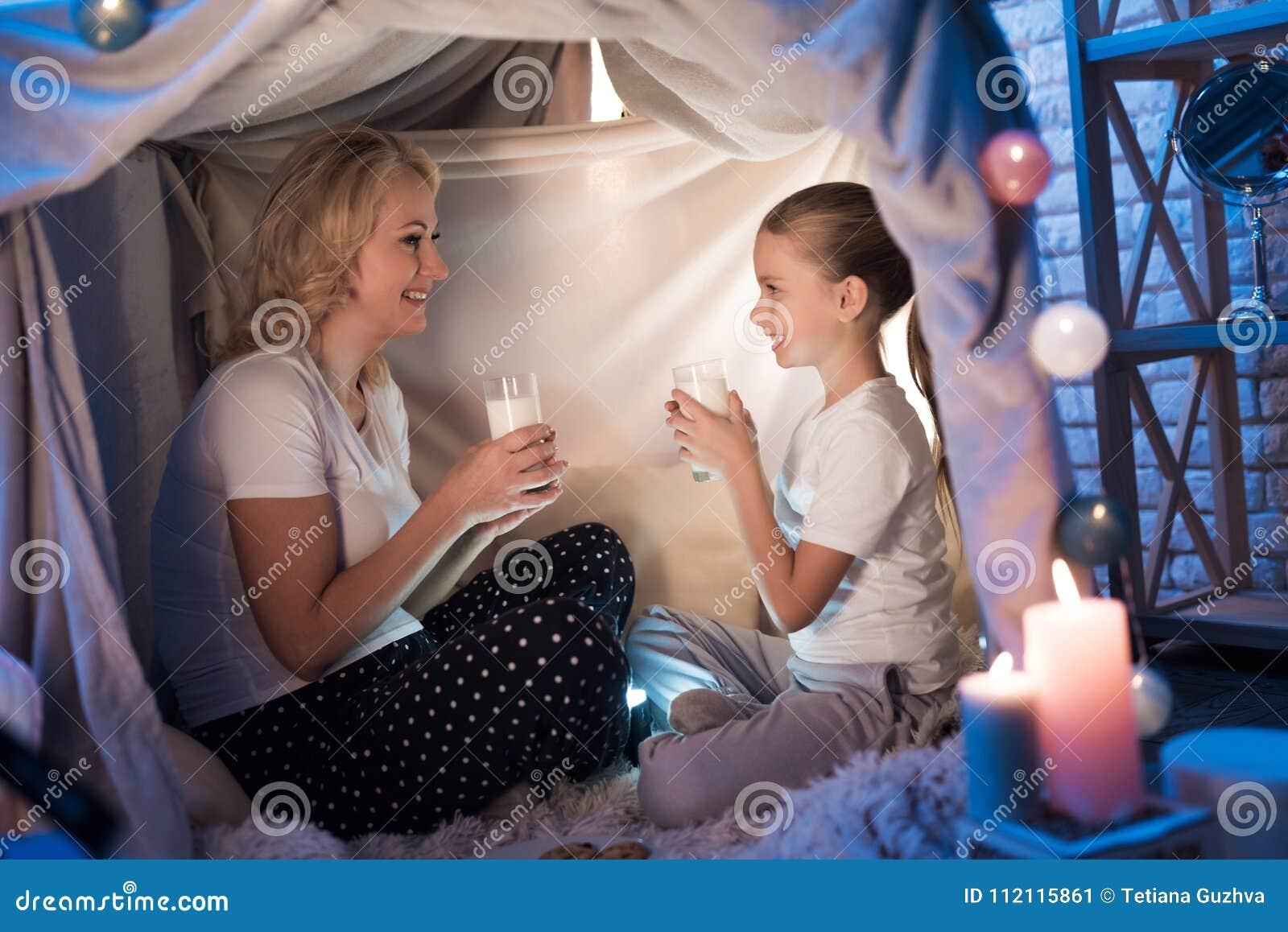 Großmutter und Enkelin essen Plätzchen mit Milch im umfassenden Haus nachts zu Hause