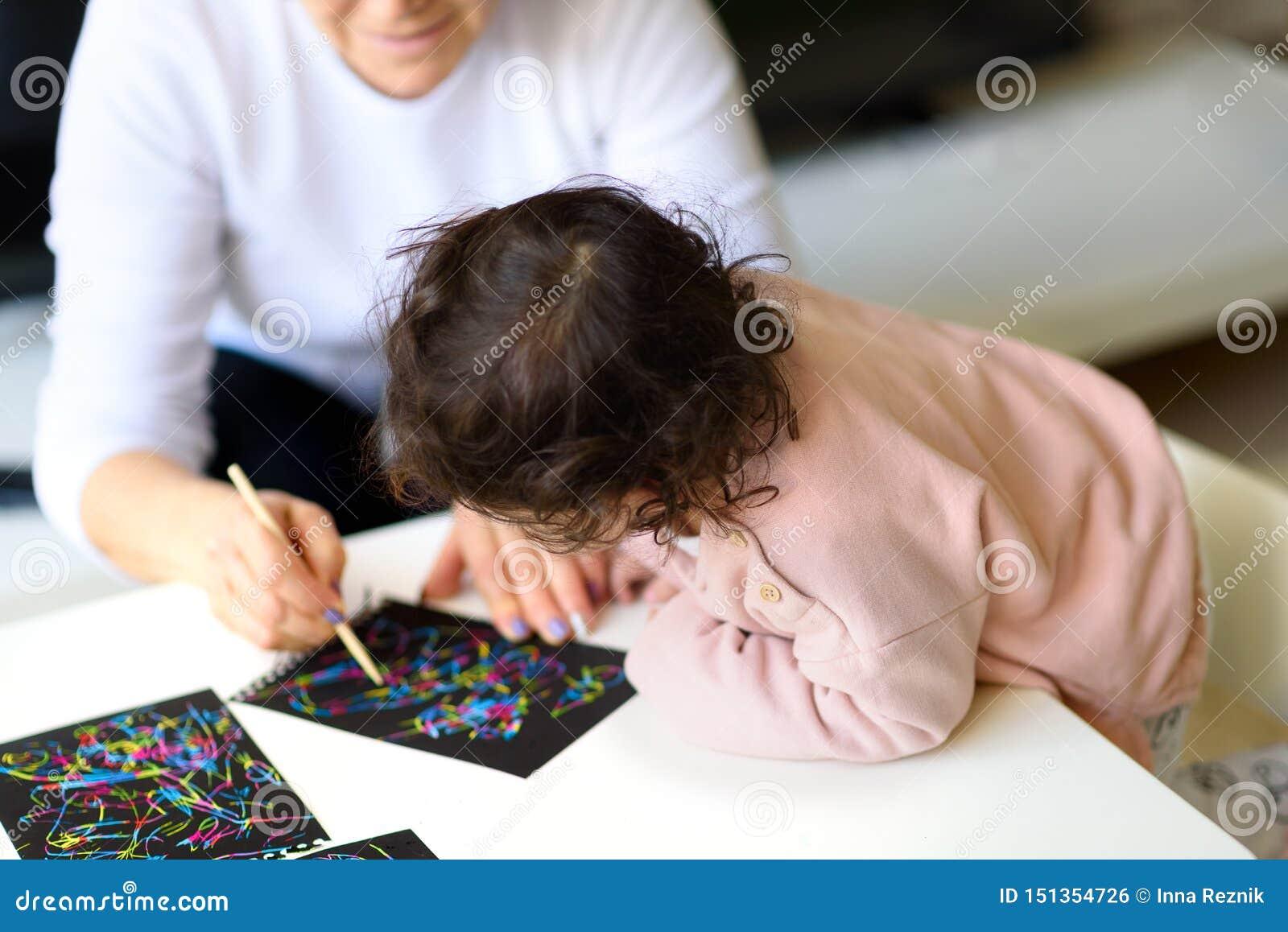 Großmutter- und Enkelinzeichnung zusammen mit Stock auf malendem Papier des magischen Kratzers zu Hause oder in der Klasse