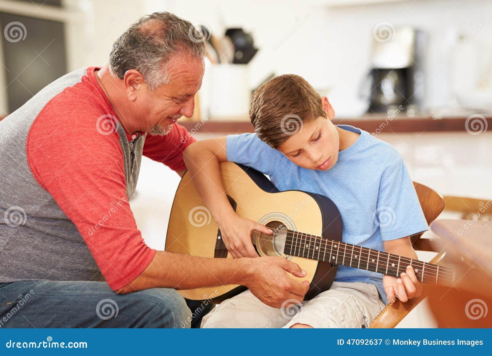 Großväterlicher unterrichtender Enkel, zum der Gitarre zu spielen