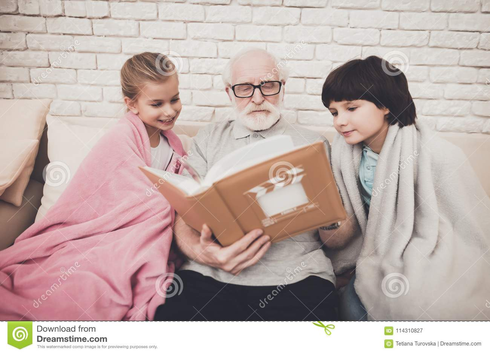 Großvater, Enkel und Enkelin zu Hause Großvater und Kinder passen Fotos im Album auf
