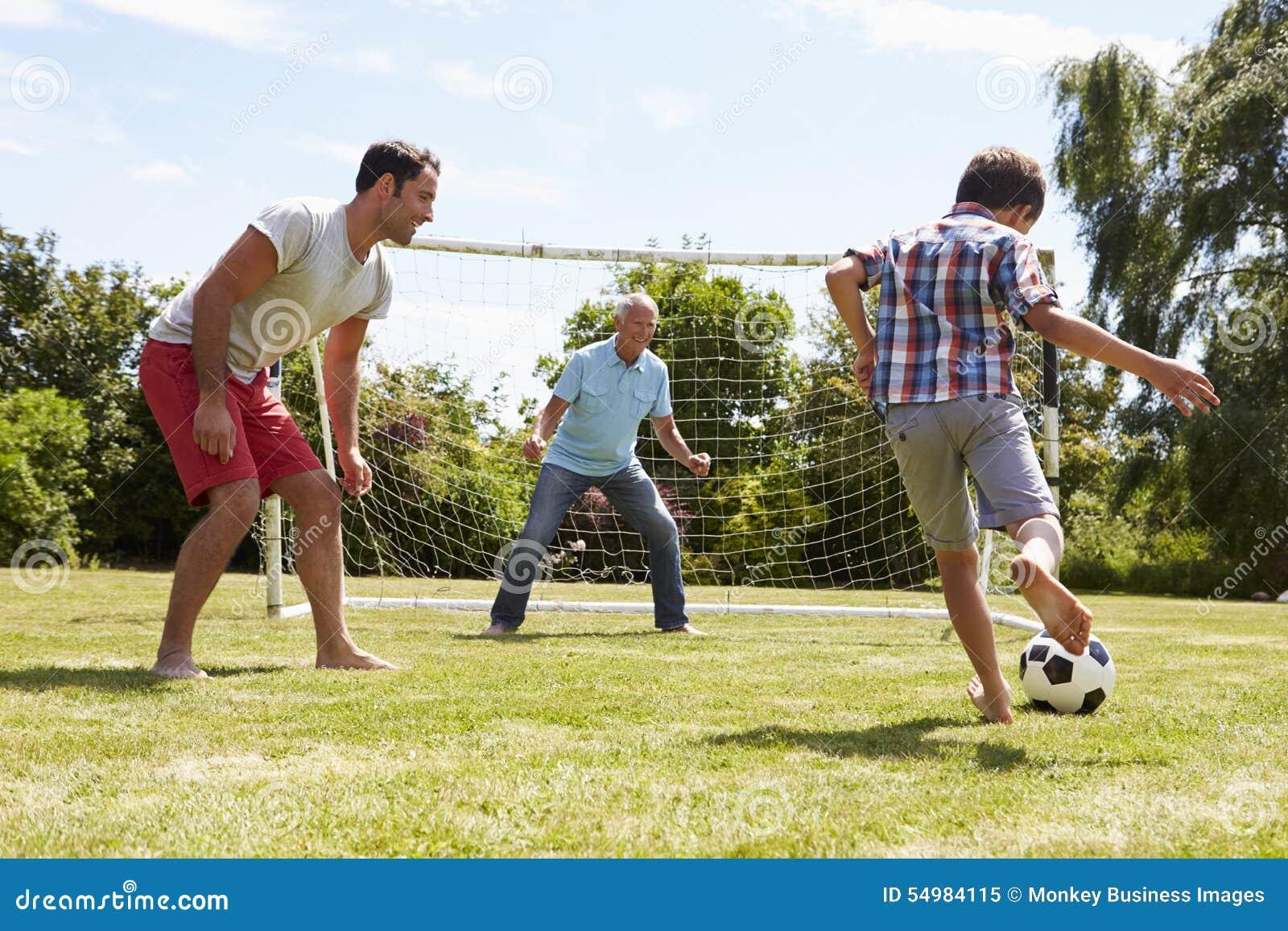 Großvater-, Enkel-und Vater-Playing Football In-Garten