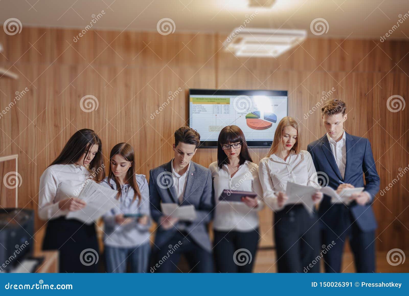 Gro?es Team von Leuten arbeitet bei einem Tisch f?r Laptops, Tabletten und Papiere, auf dem Hintergrund ein gro?er Fernseher auf