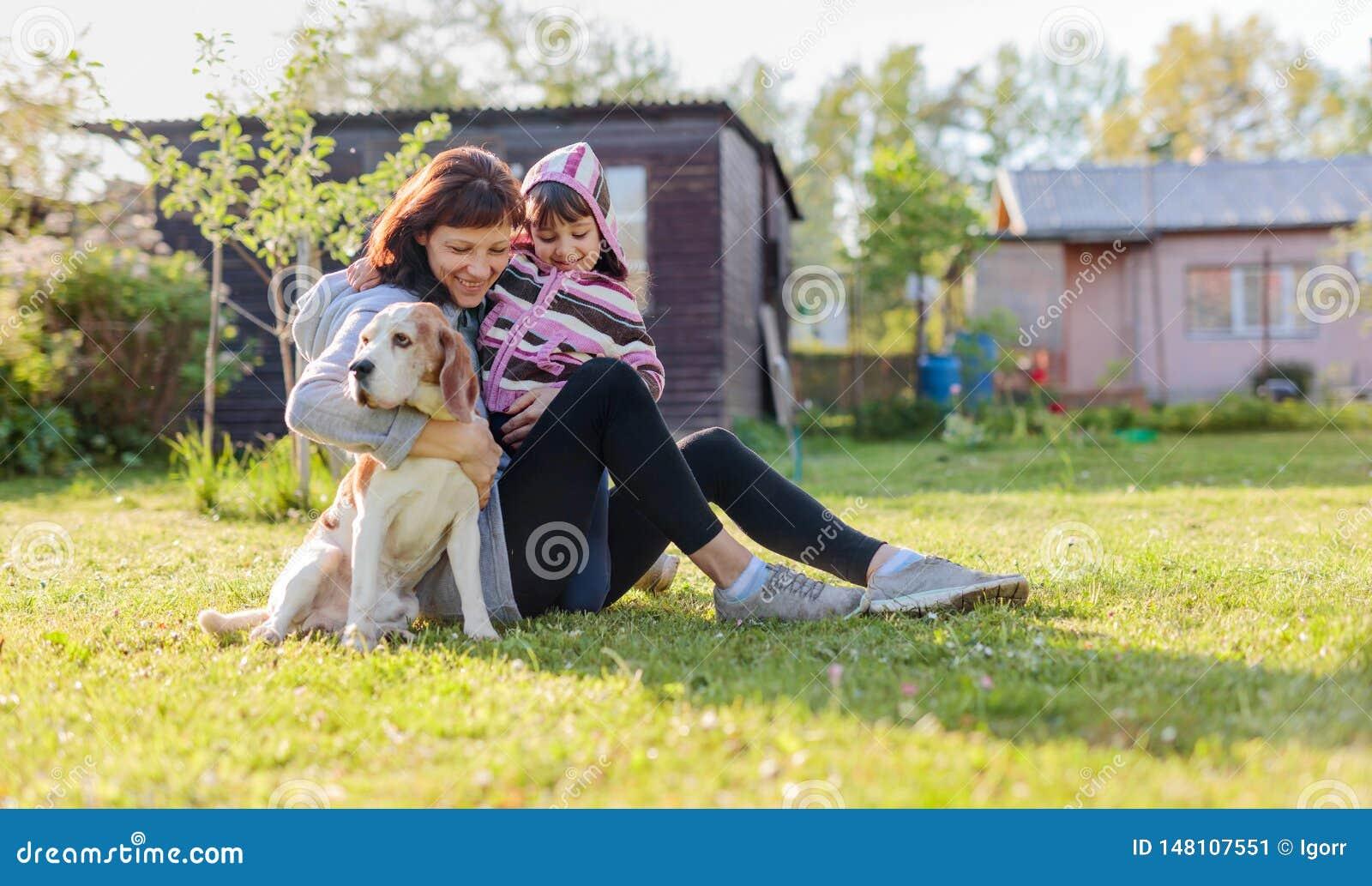 Gro?mutter mit der Enkelin und Hund, die auf dem ein Sonnenbad nehmenden Rasen spielen
