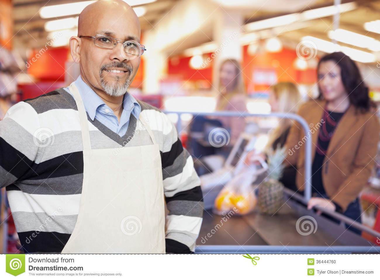 Grocery Store Cashier Standing At Checkout Counter Stock