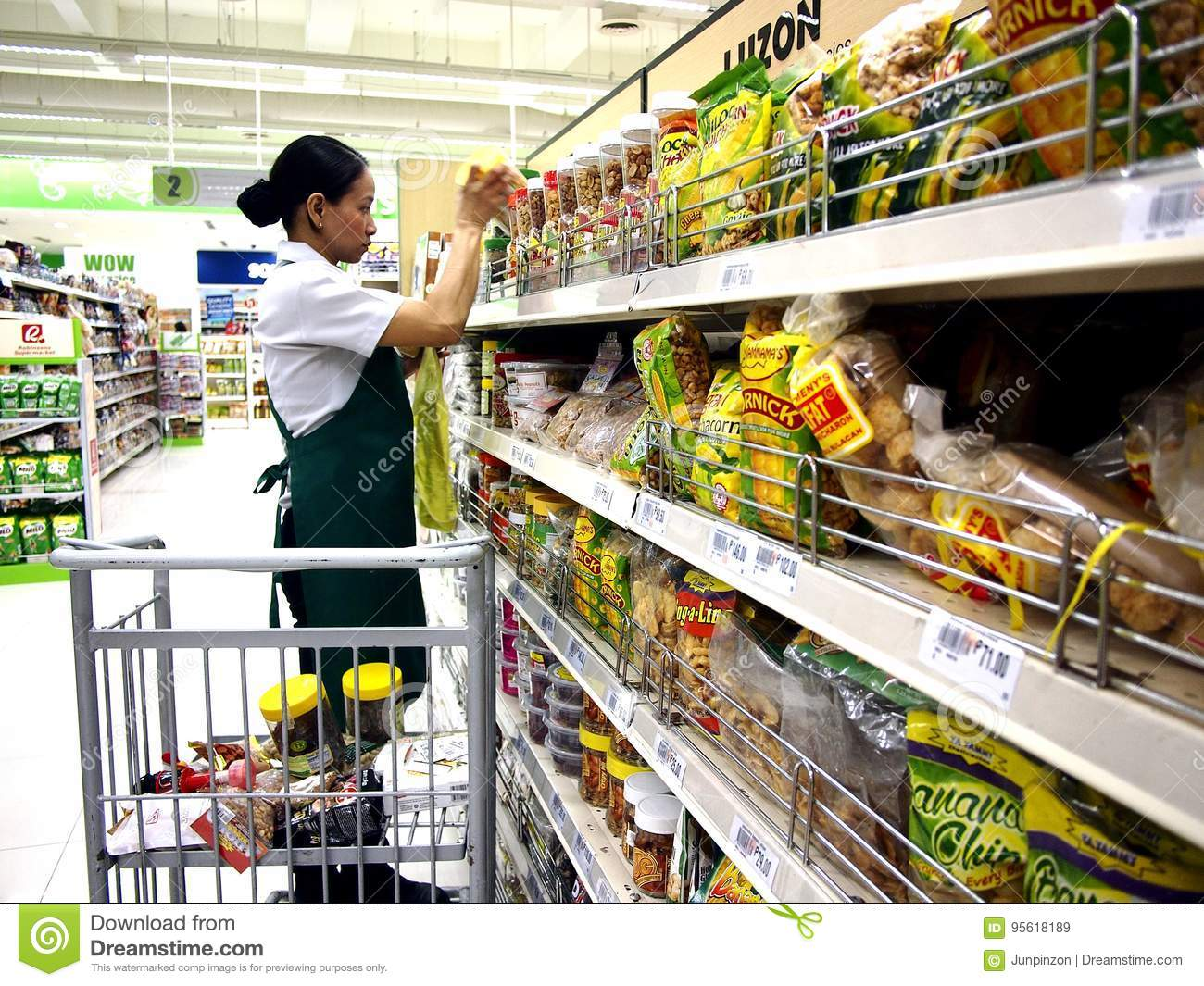 A Grocery Store Worker Refills The Shelves With New Stocks Of