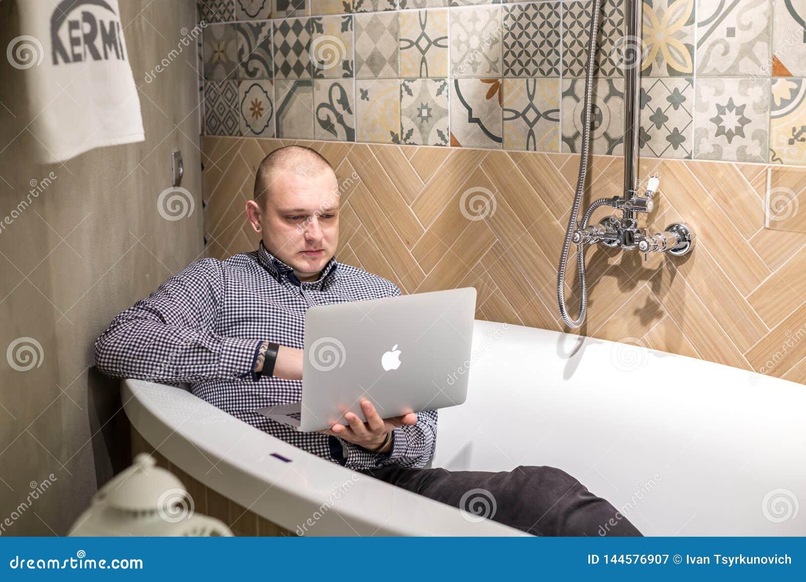 GRODNO, БЕЛАРУСЬ - МАРТ 2019: работники молодого человека кладут в ванну с ноутбуком в современном роскошном паяя магазине