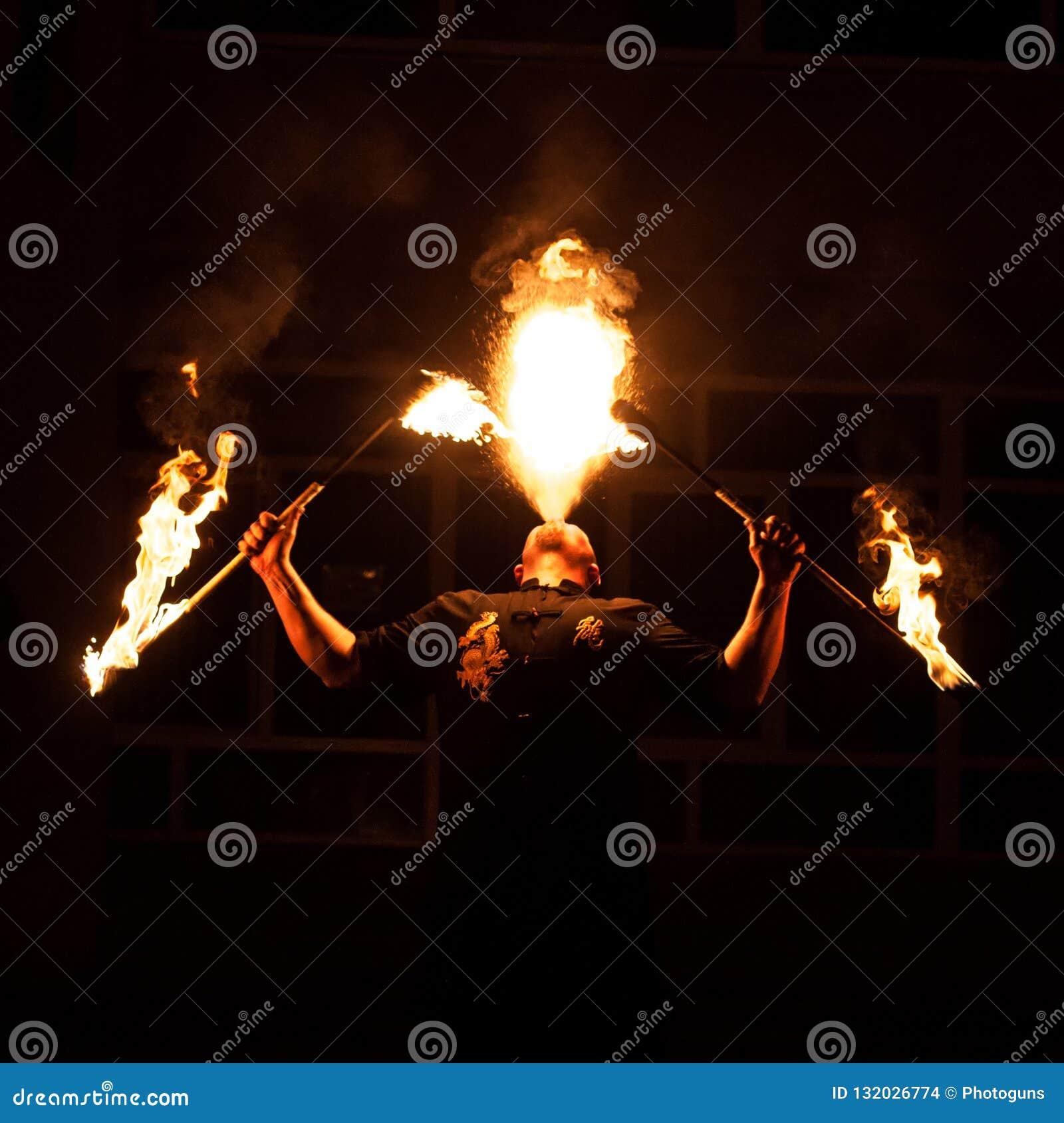 Grodno, Białoruś - Kwiecień, 30, 2012 pożarniczy przedstawienie, pożarniczy podmuchowy występ, tanczy z płomieniem, samiec mistrz