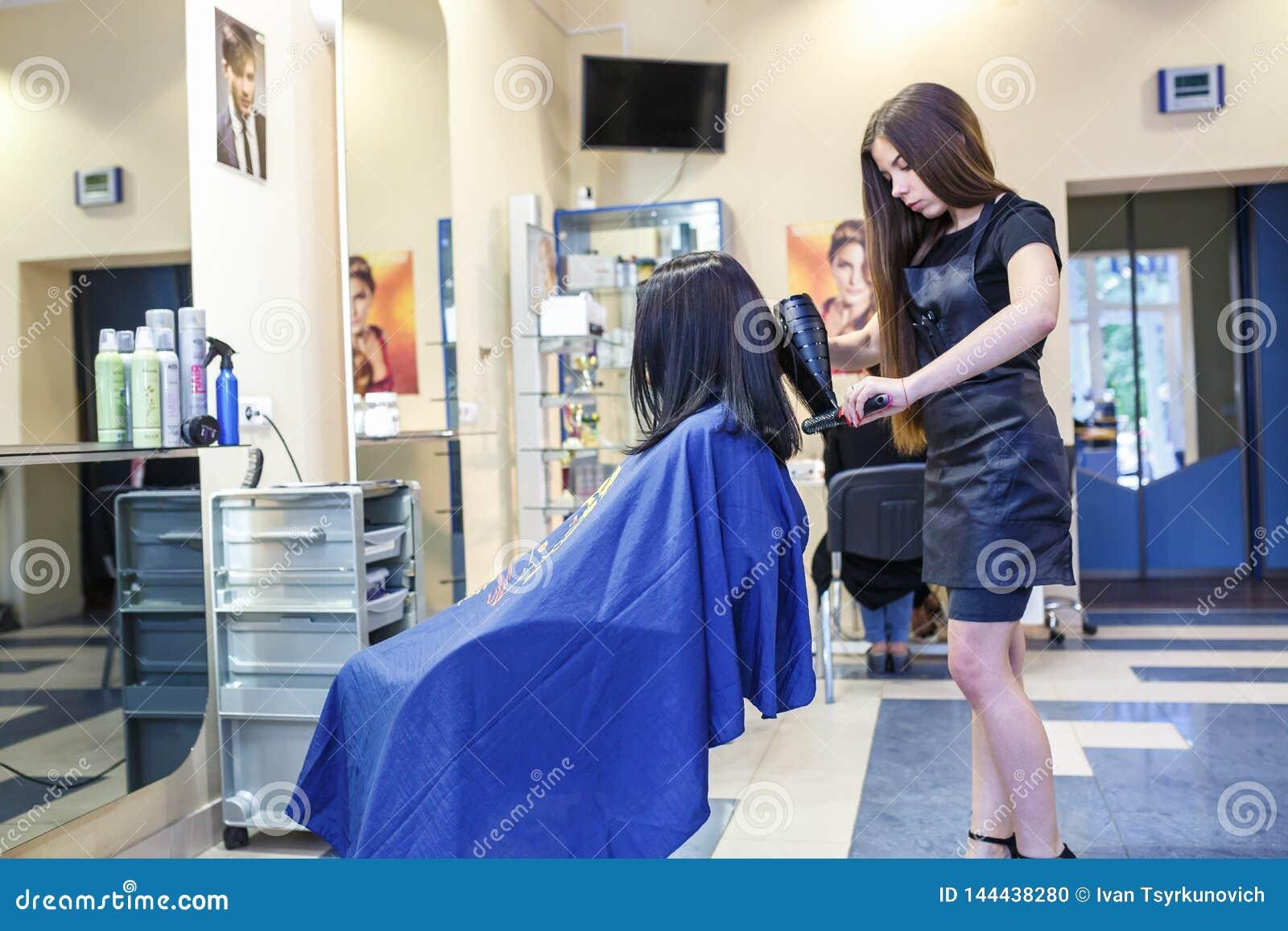 GRODNO BIAŁORUŚ, MAJ, - 2016: mistrzowski fryzjera coiffeur robi fryzurze w fryzjera męskiego salonie dla młodej kobiety