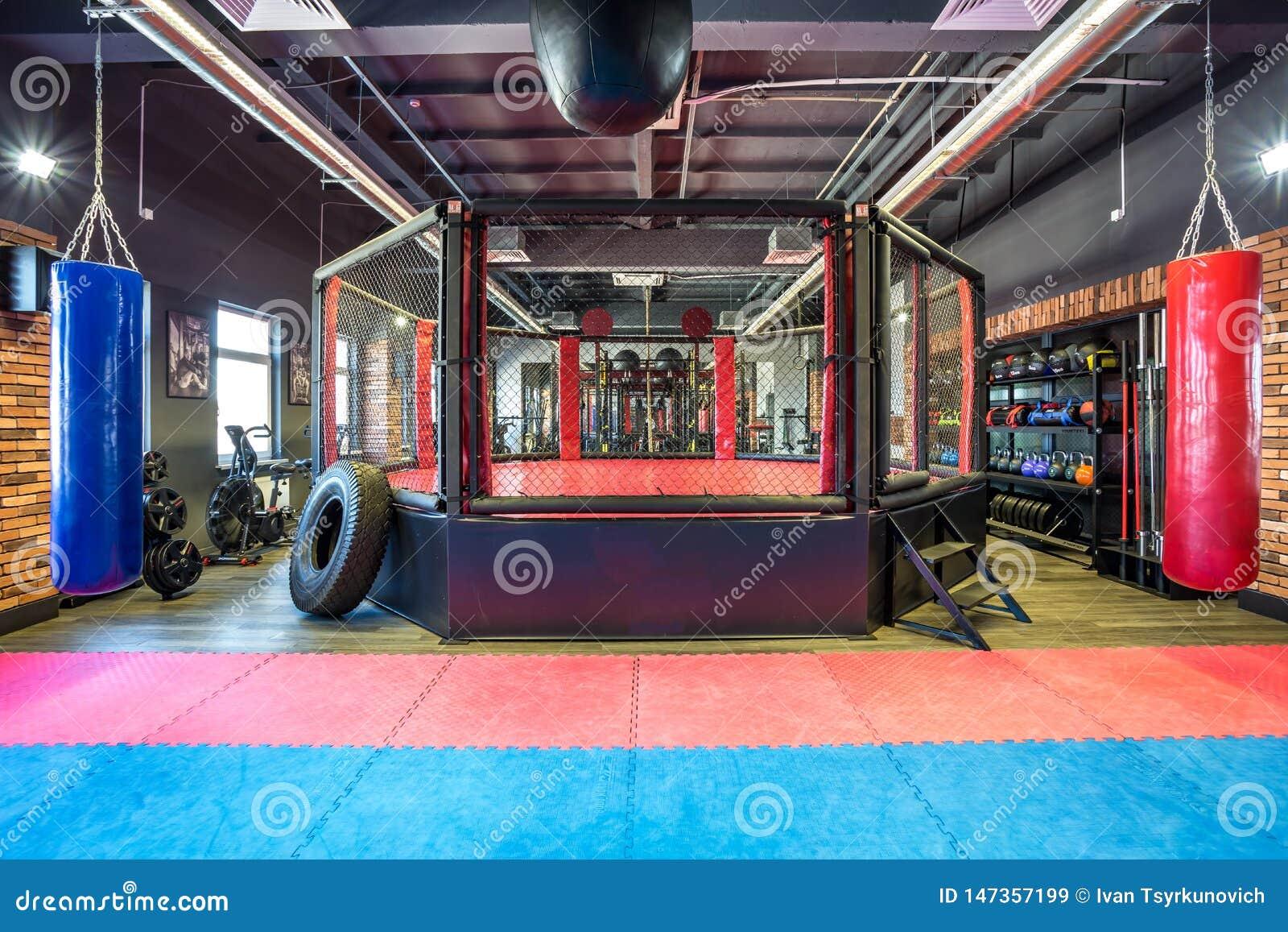 GRODNO, BIELORRUSIA - ABRIL DE 2019: Pasillo de artes marciales con el anillo y los sacos de arena que luchan en el club moderno
