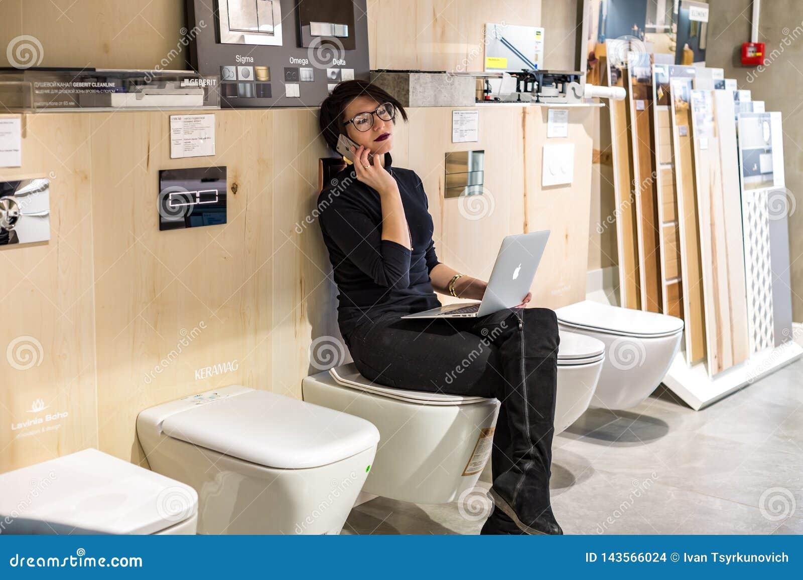 GRODNO, BIELORRUSIA - MARZO DE 2019: empleados de mujer joven en los trabajos de cristal en el ordenador en tienda moderna con el