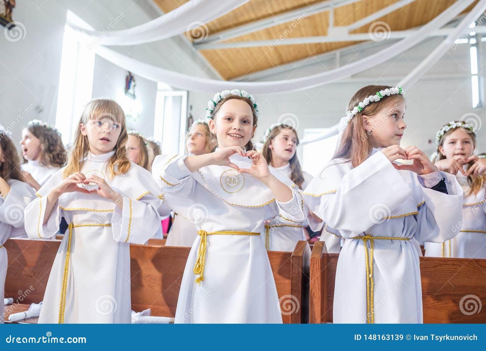 GRODNO, BIELORRUSIA - MAYO DE 2019: Los ni?os jovenes en la iglesia cat?lica est?n esperando la primera comuni?n del eucharist Po