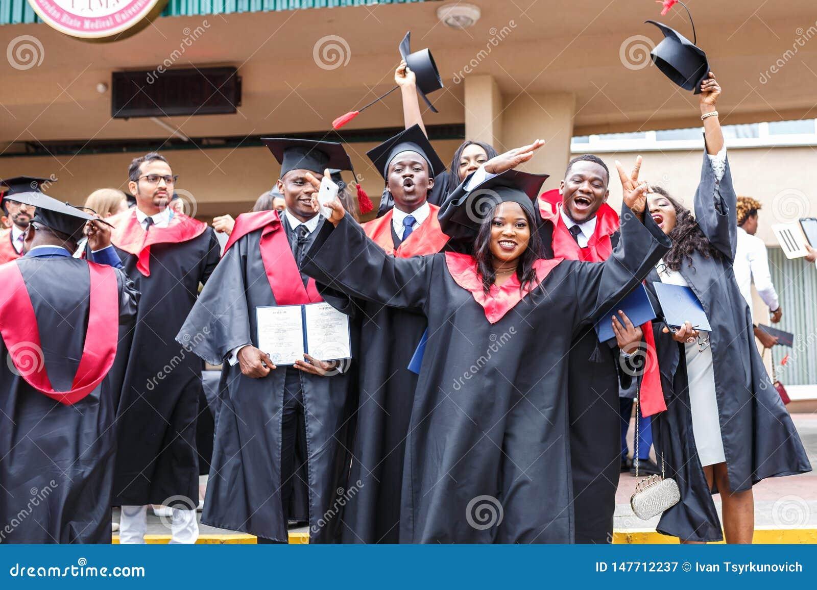 GRODNO VITRYSSLAND - JUNI, 2018: Lyckliga utländska afrikanska medicinare i fyrkantiga akademiska avläggande av examenlock och sv