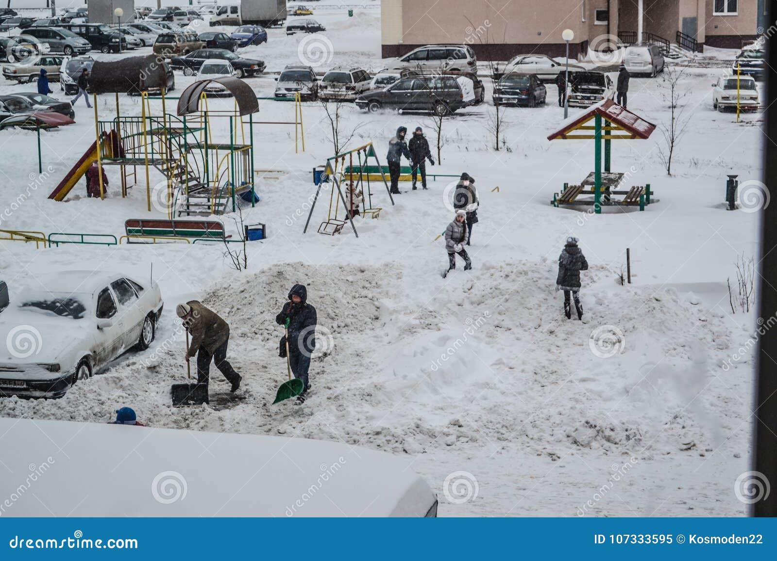 Grodno, Wit-Rusland, 12 15 2012 is Er heel wat sneeuw in de werf van het flatgebouw, het vriendschappelijke schoonmaken van de sn