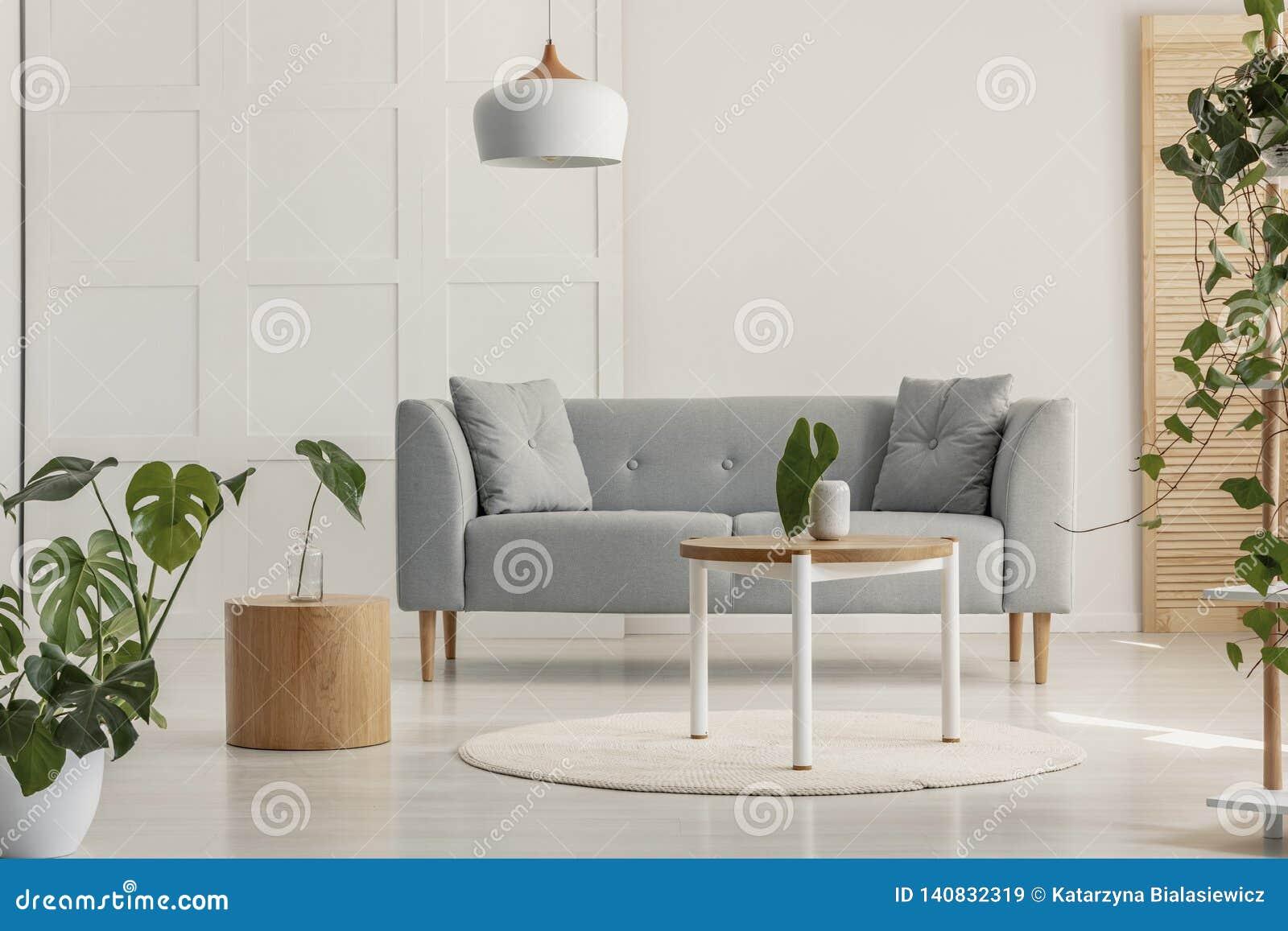 Groen blad in witte vaas op ronde houten koffietafel in modieuze woonkamer met grijze Skandinavische bank