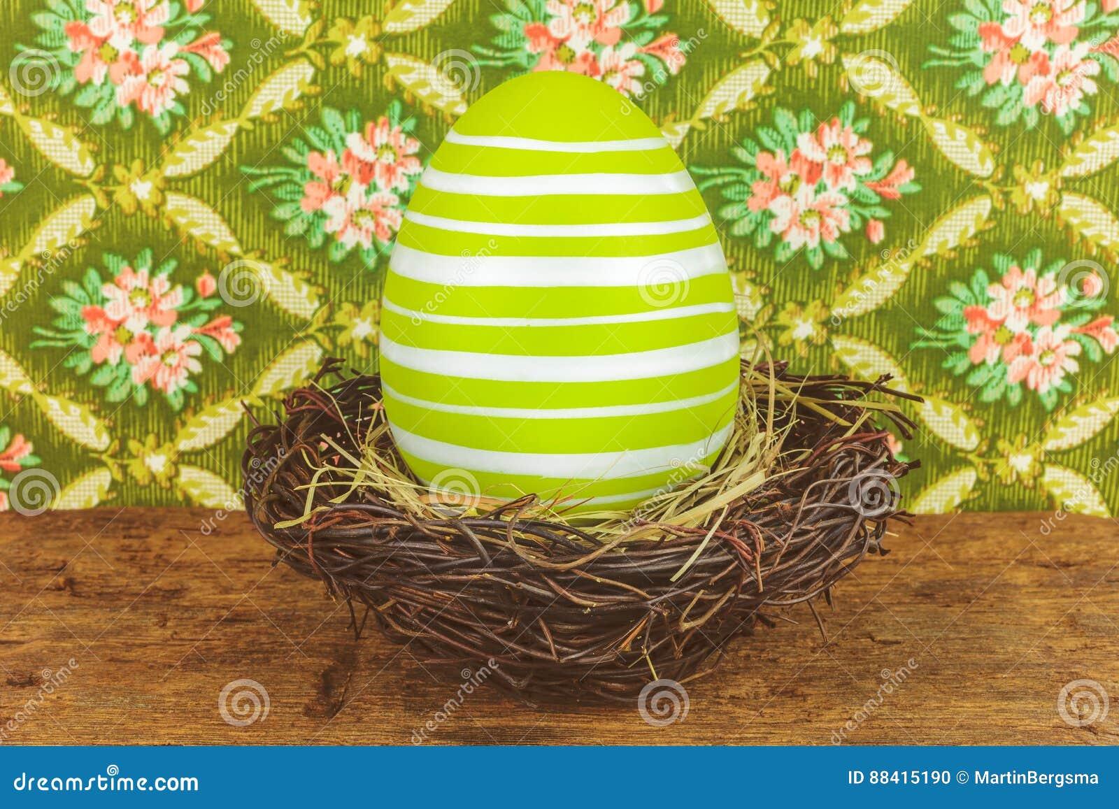 Groen geverft groot paasei in een vogelnest op een houten lijst