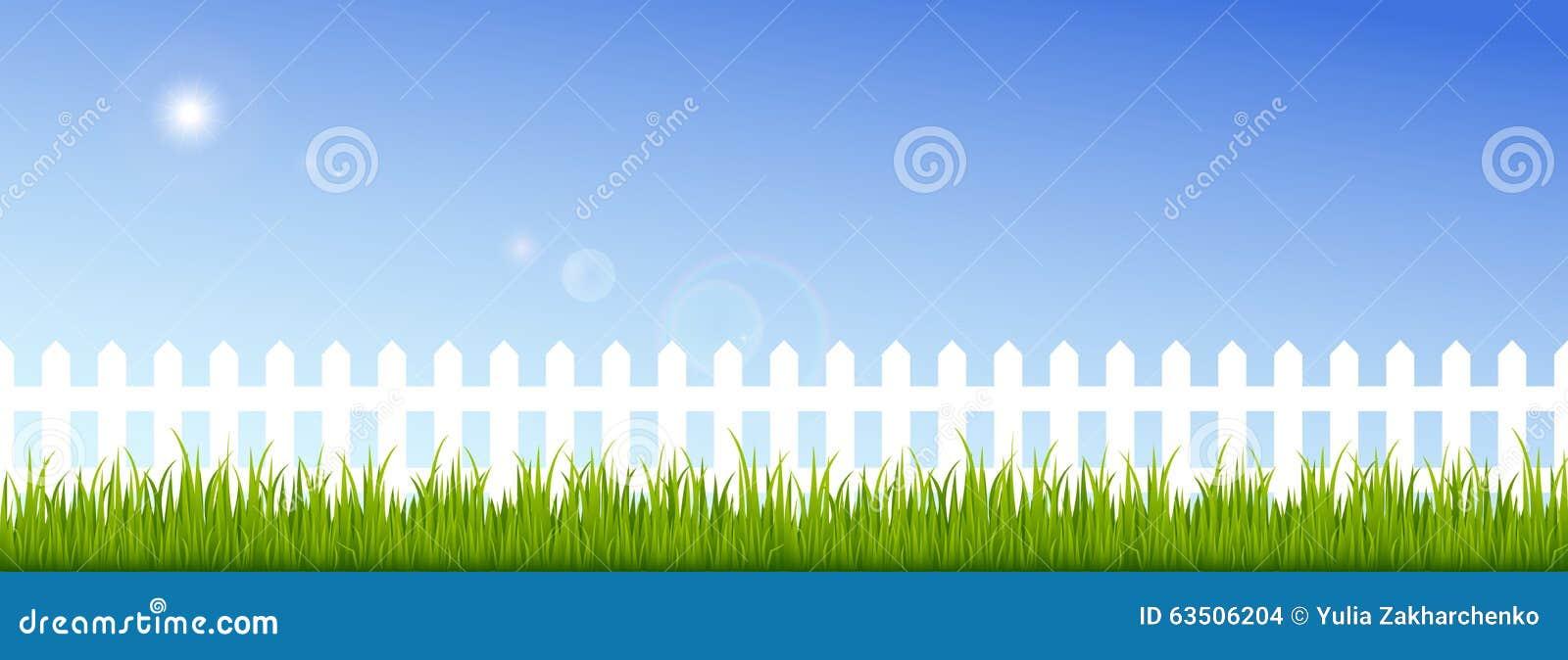 Groen gras en witte omheining op een duidelijke blauwe hemel