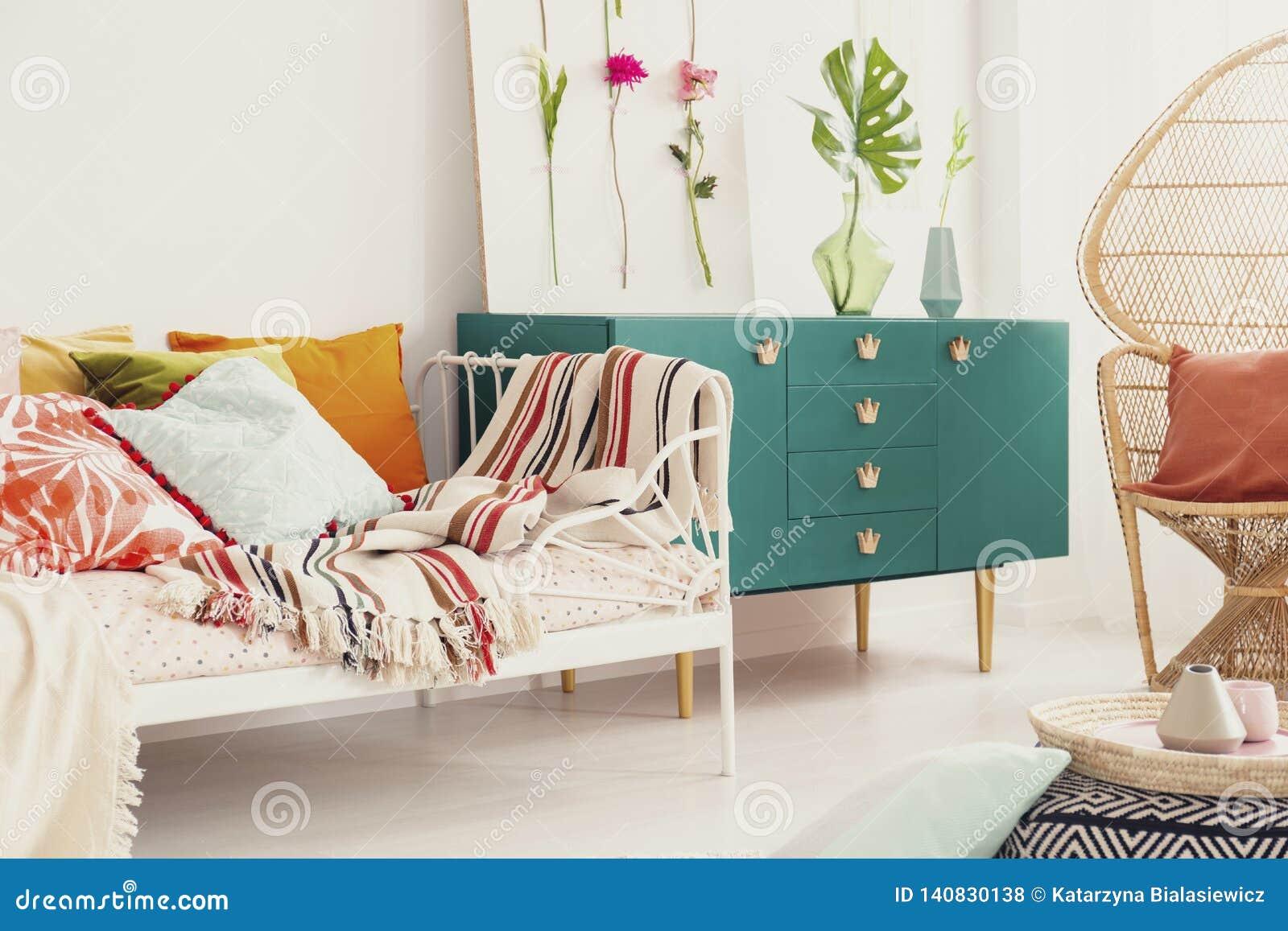 Groen kabinet met het handvat van de kroonvorm in het midden van heldere slaapkamer met kleurrijk beddegoed op de bed en rotanpau