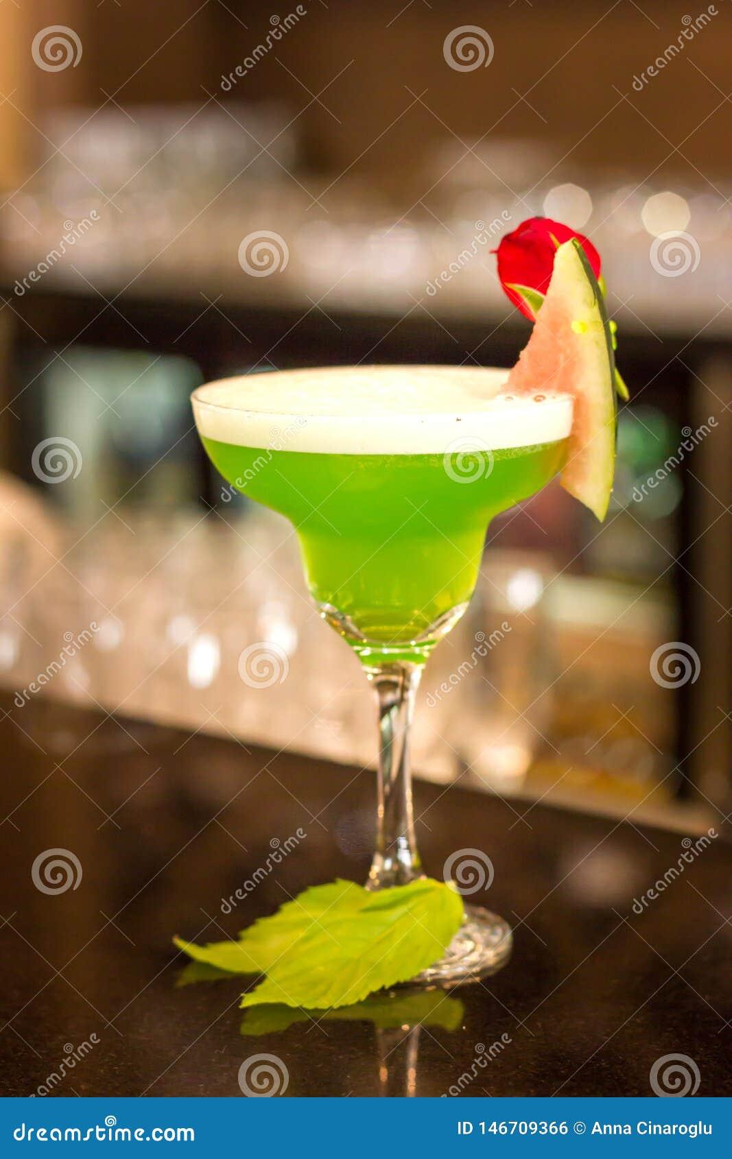 Groene alcoholische cocktail met munt in een glas van Margarita op een barteller