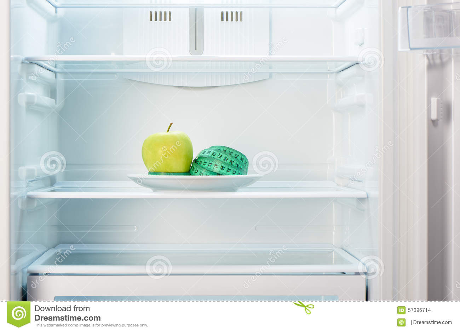 Groene appel met het meten van band op witte plaat in open lege ijskast