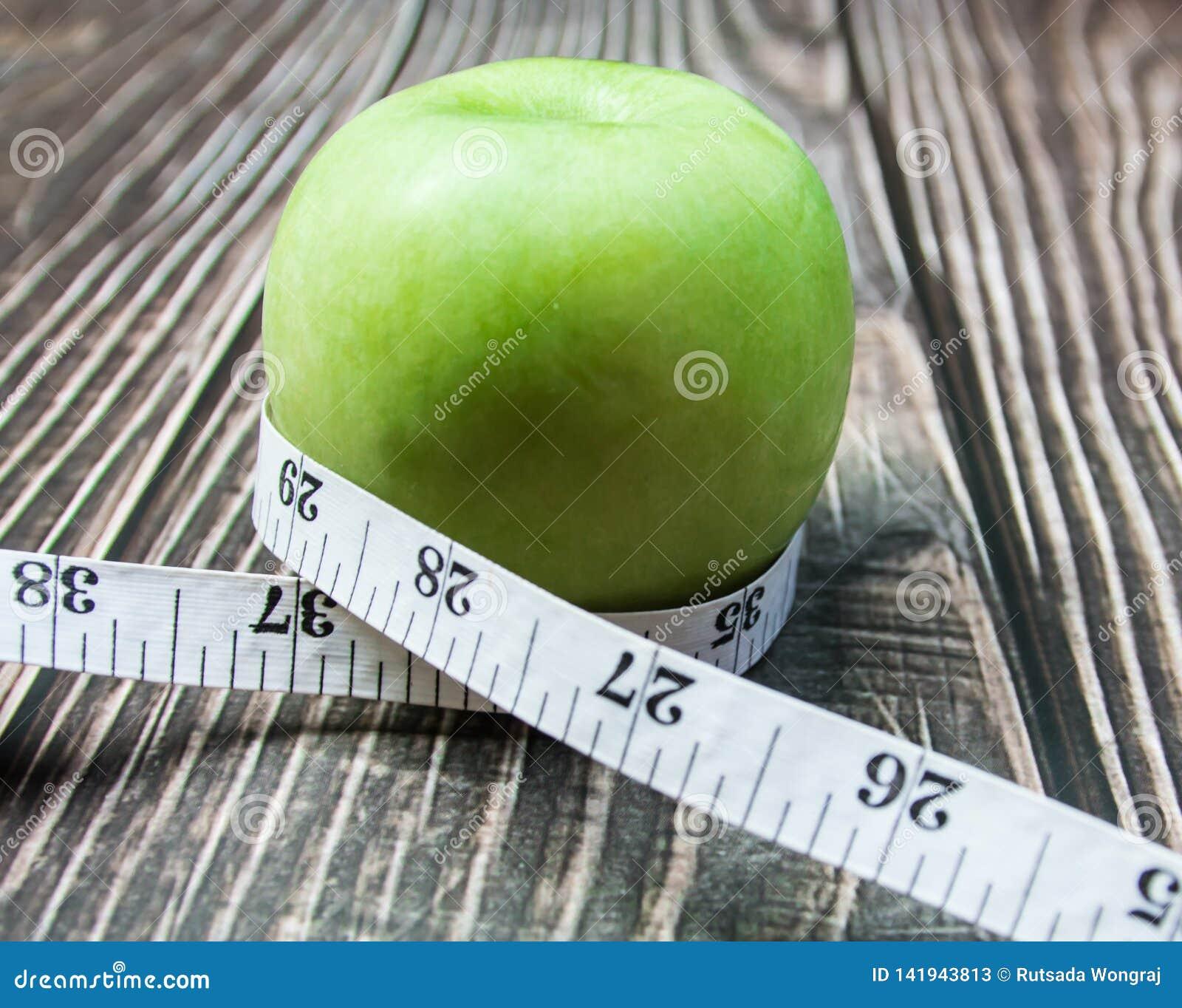 Groene appel met meting op het hout