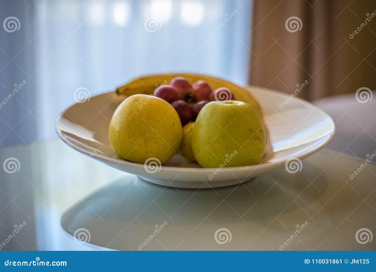Groene appelen, druiven en banaan op witte lijst