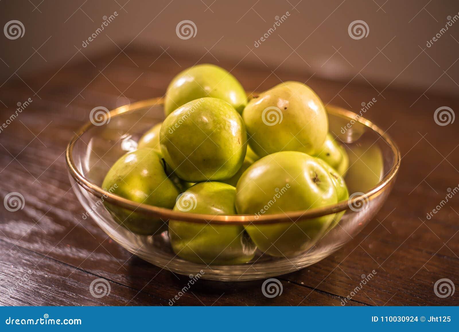 Groene appelen in duidelijke kom op lijst