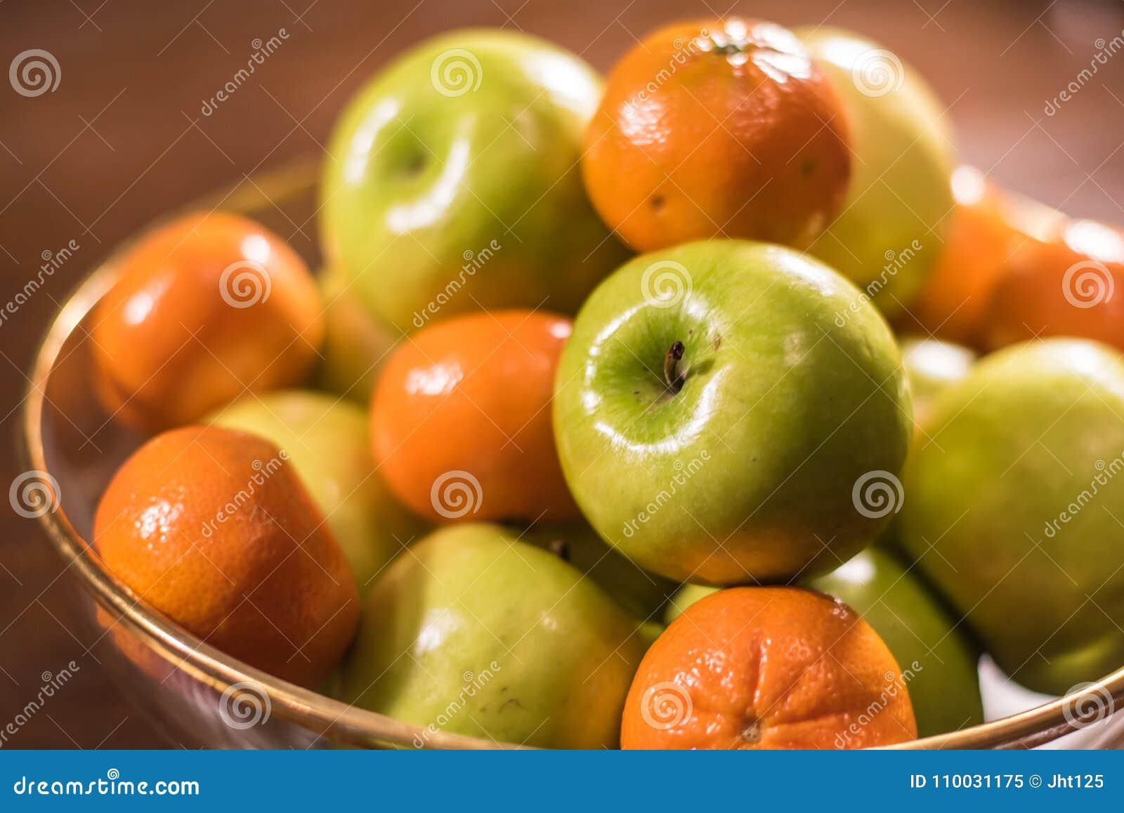 Groene appelen en sinaasappelen in duidelijke kom op lijst